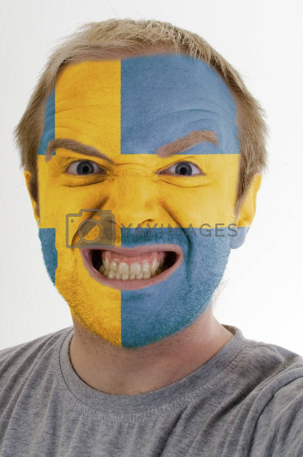 High key portrait of an angry man whose face is painted in colors of swedish flag