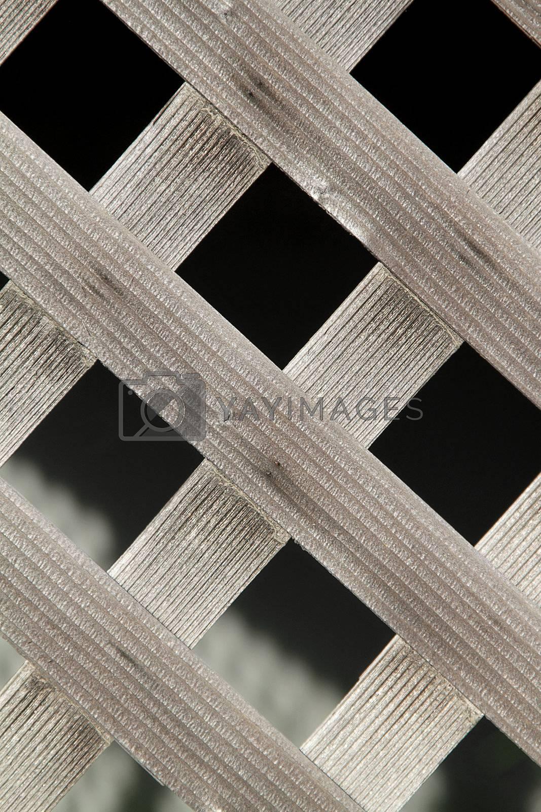 Old wooden diagonal fence over dark background