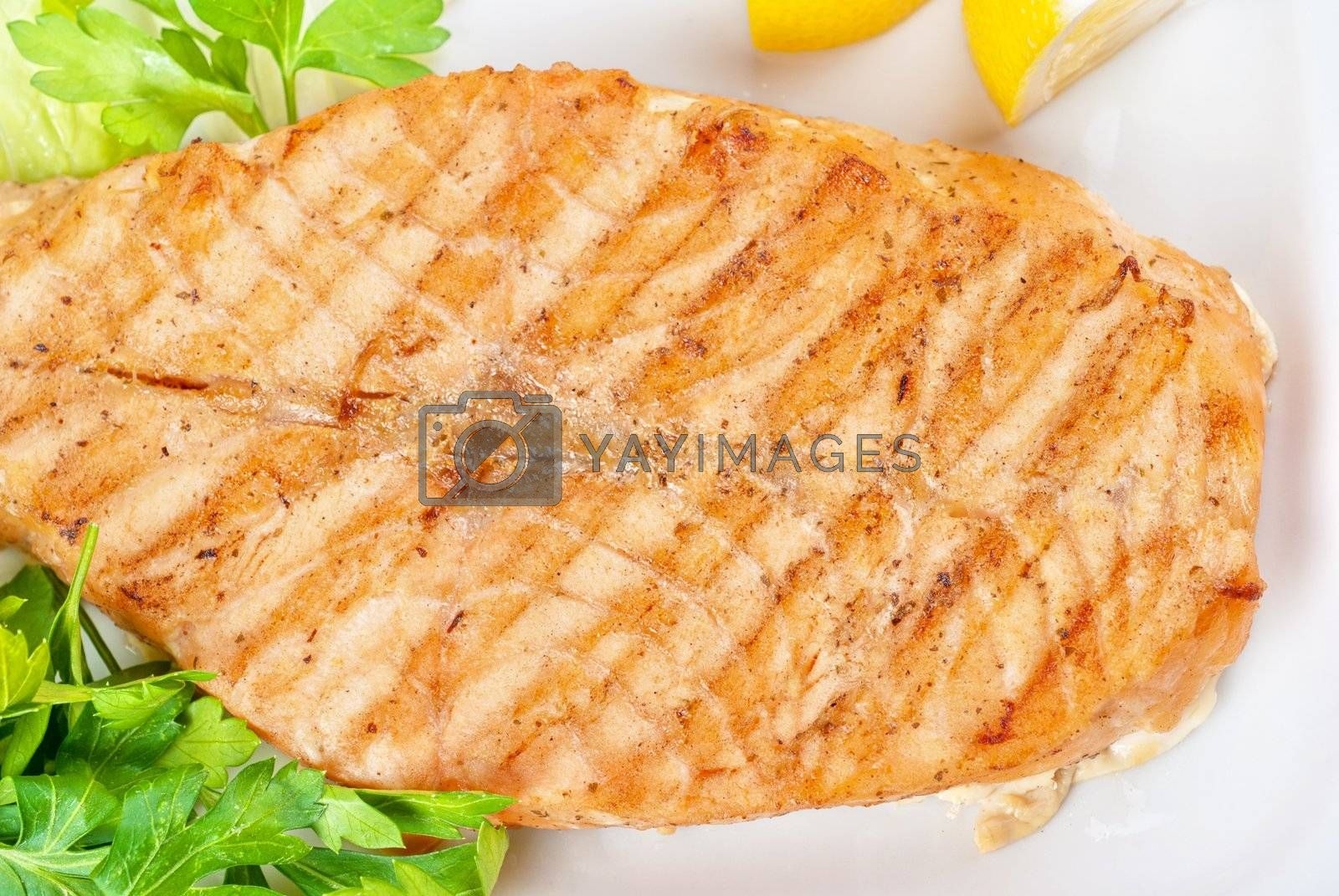 Grilled salmon steak with greens,onion, lemon, lime and olive