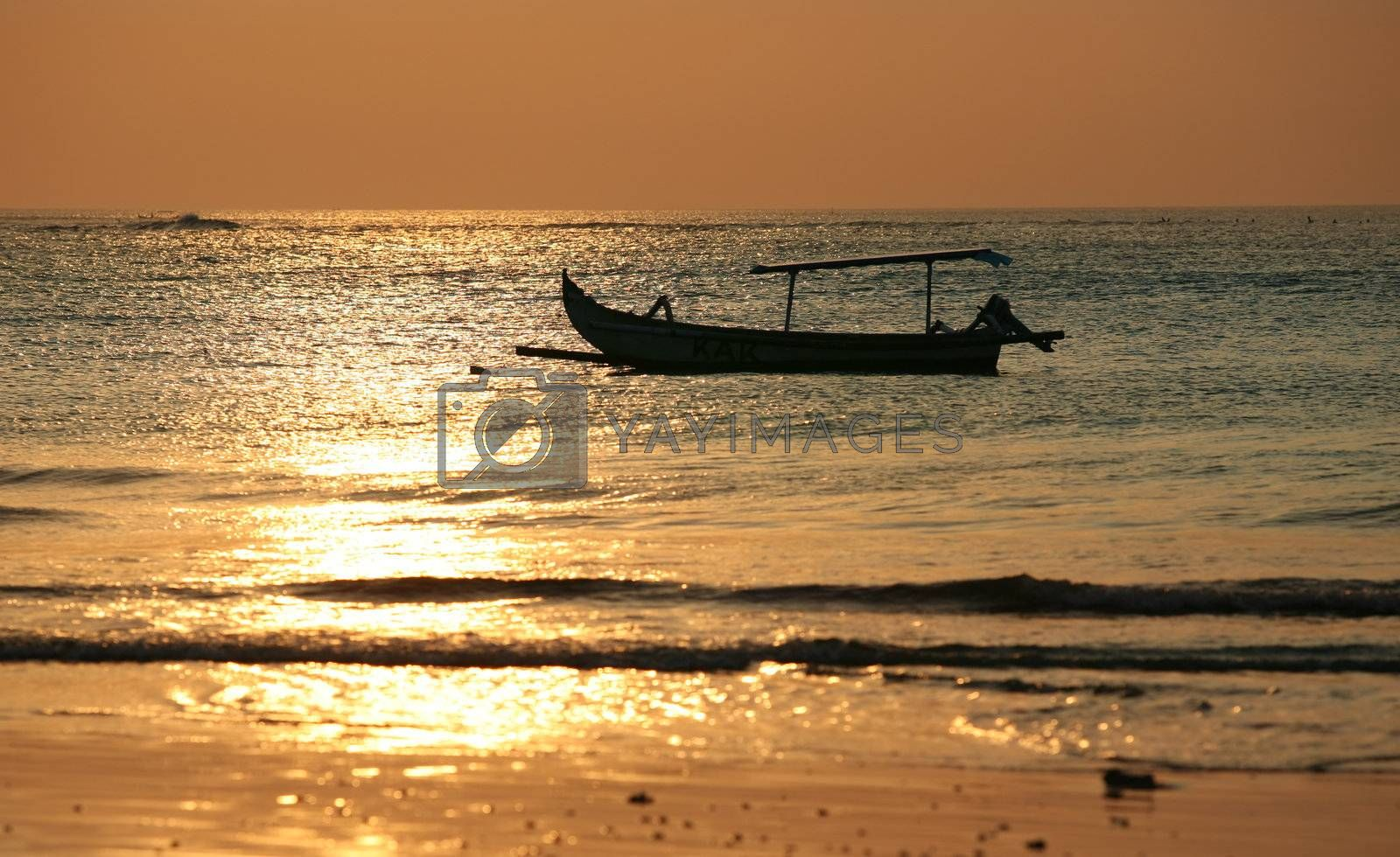 Drifting boat on a sunset. Coast of the Indian ocean. Bali