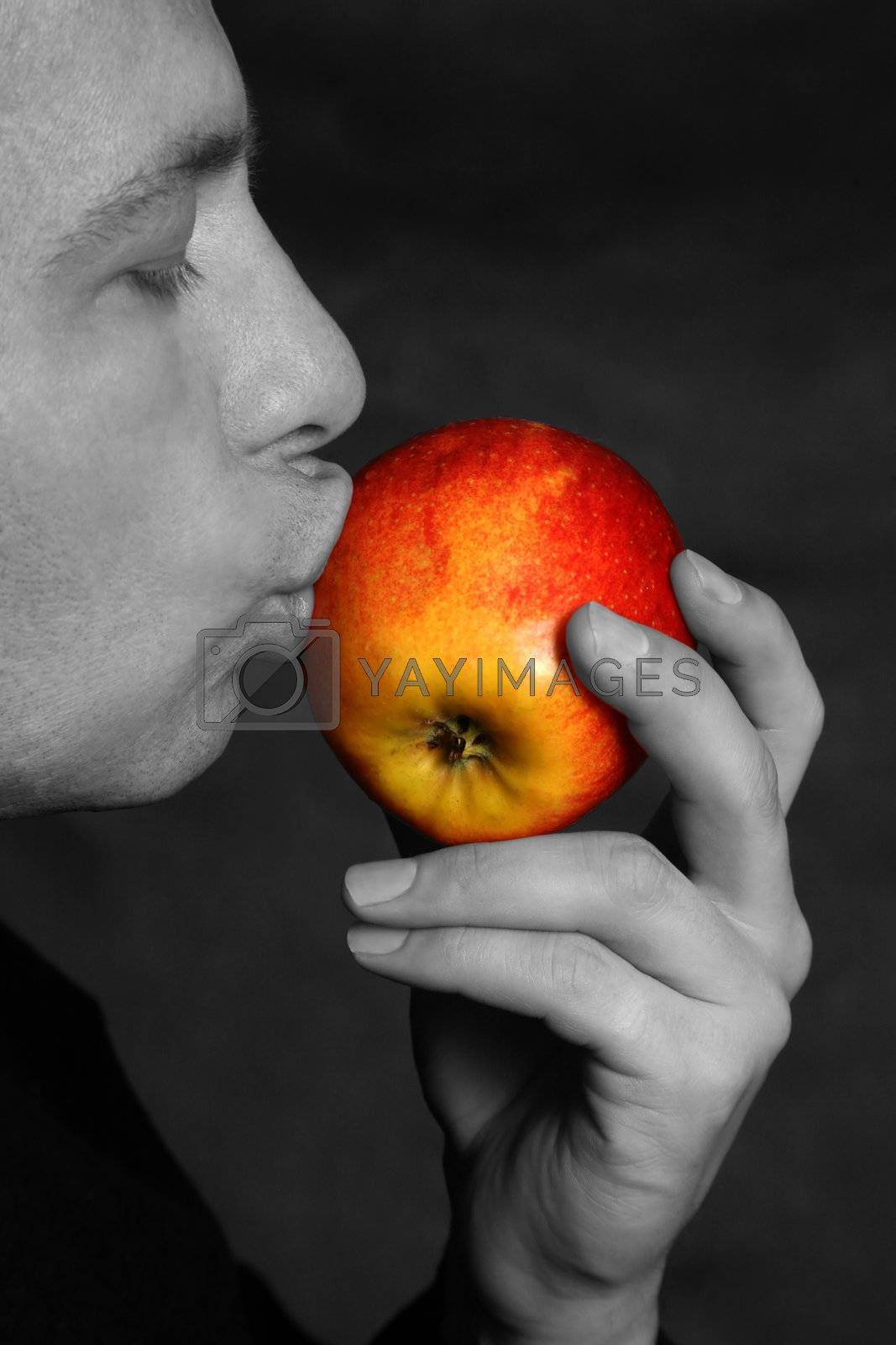 The man concerns lips of a red apple