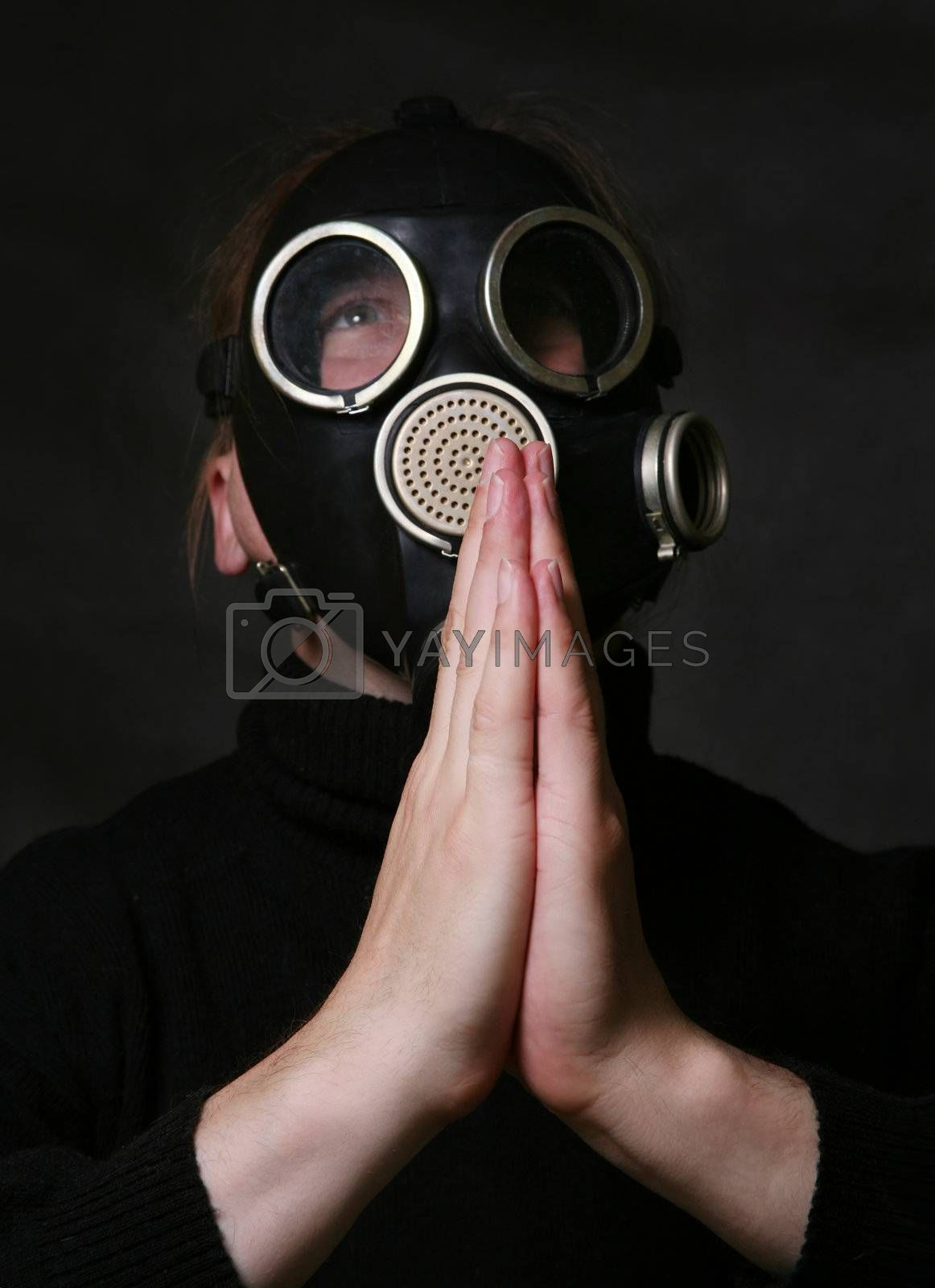 The man in a gas mask on a dark background. Hands are combined as at prayer