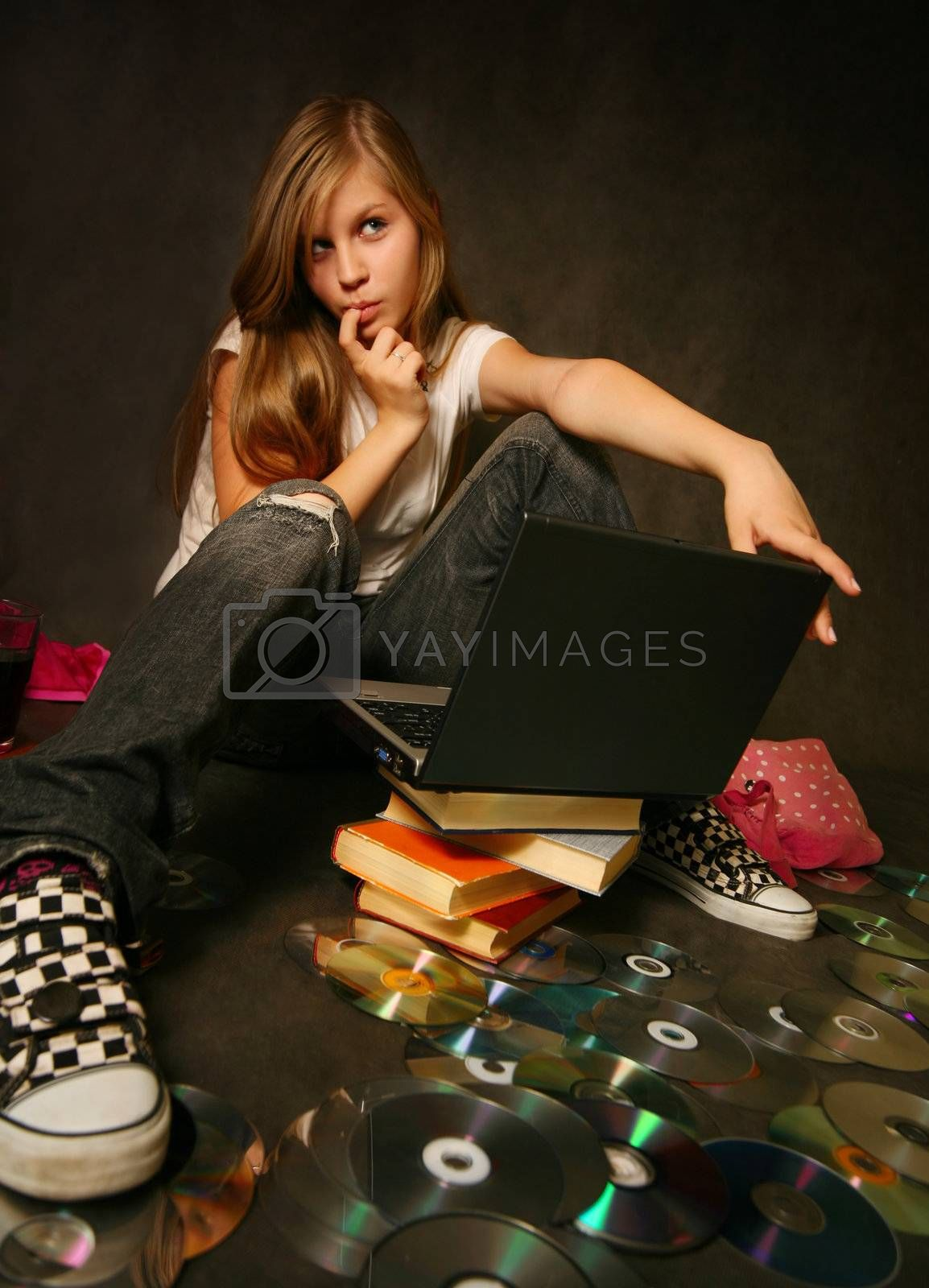 The young girl among books with a computer
