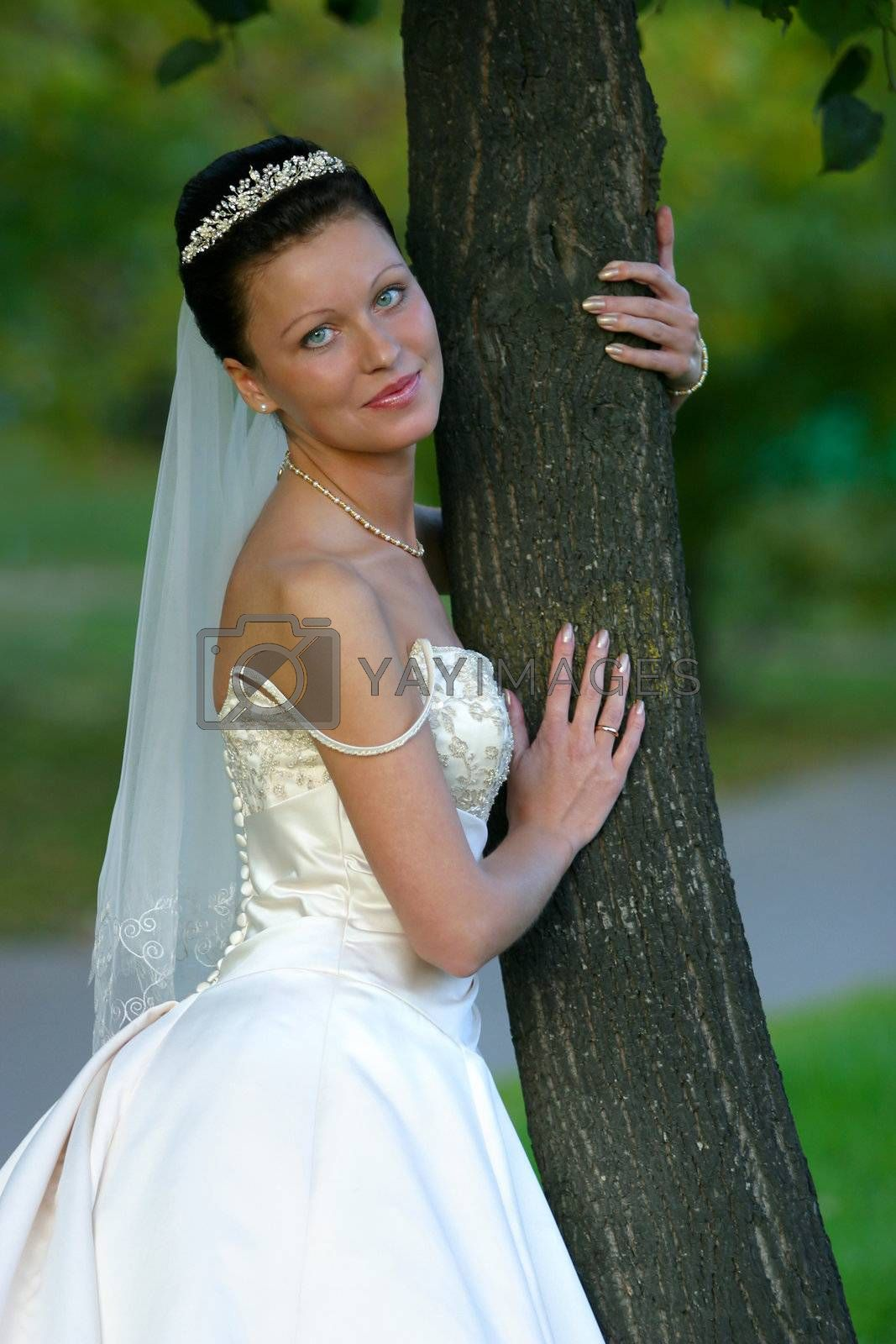 Portrait of the beautiful bride worth near a tree