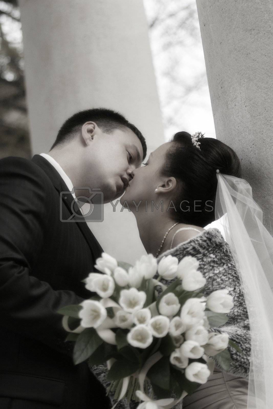 Beautiful the bride and the groom kiss at columns