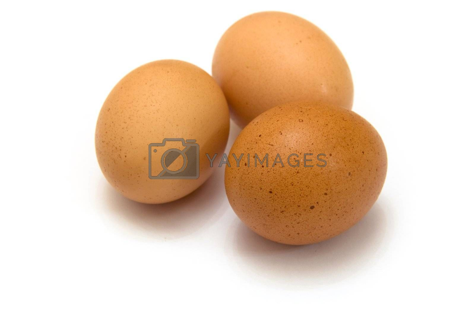 Three eggs lying down on a white linen background