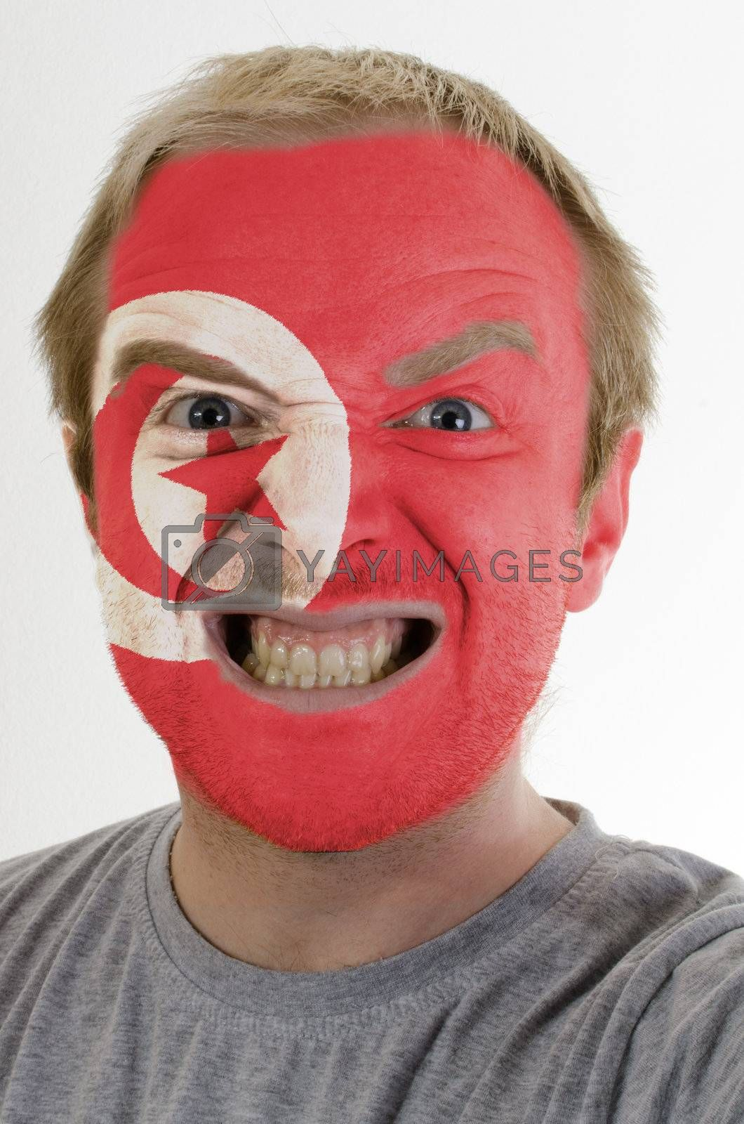 High key portrait of an angry man whose face is painted in colors of tunisia flag