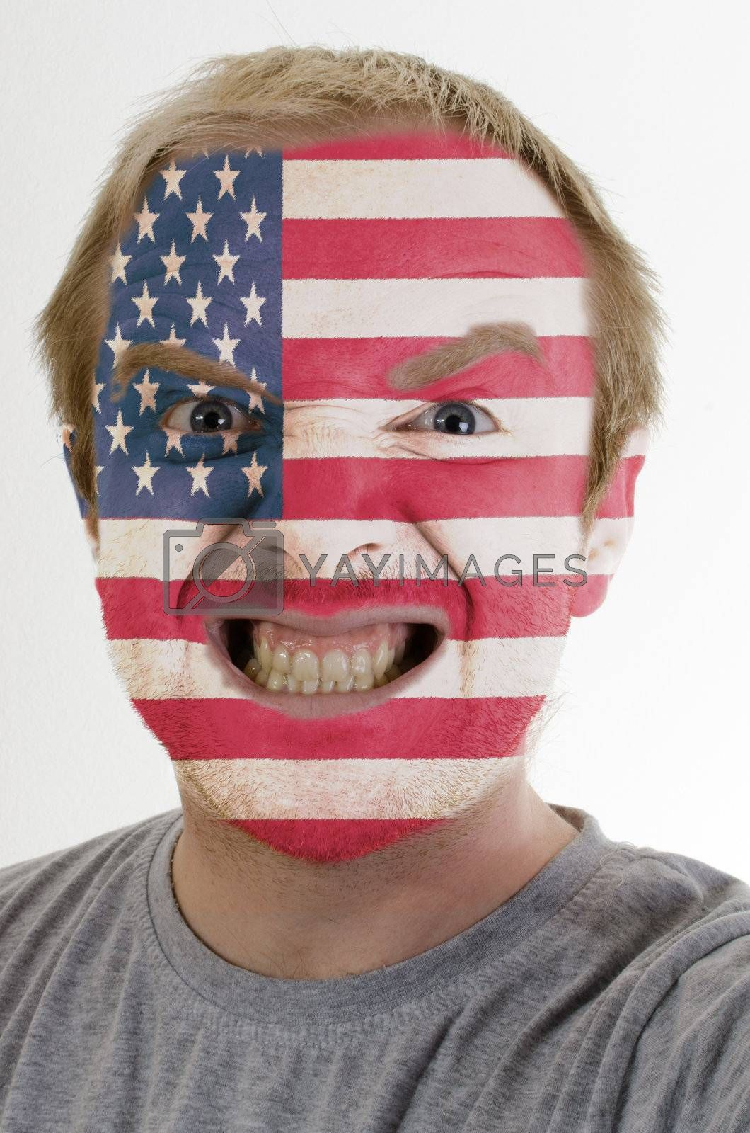 High key portrait of an angry man whose face is painted in colors of american flag