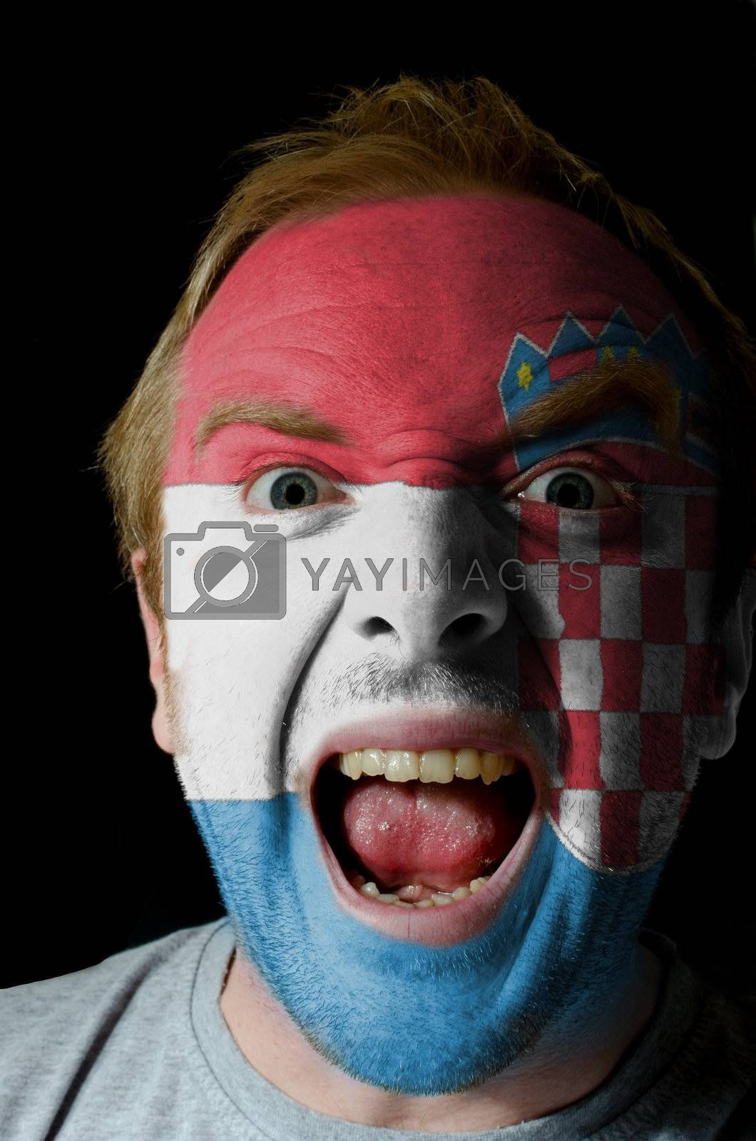 Low key portrait of an angry man whose face is painted in colors of croatian flag