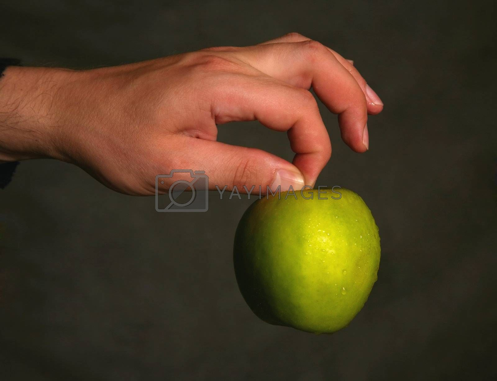 Man's hand with a green apple on a dark background