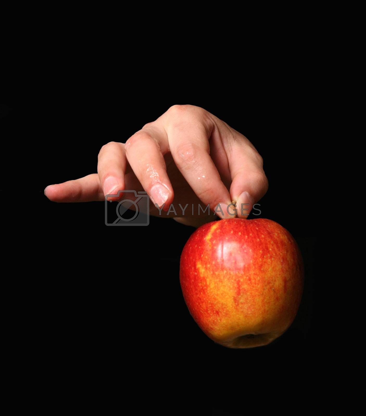 Man's hand with a red apple on a black background