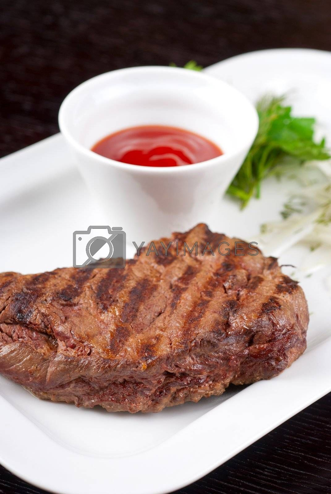 Juicy roasted beef steak with vegetables closeup at plate