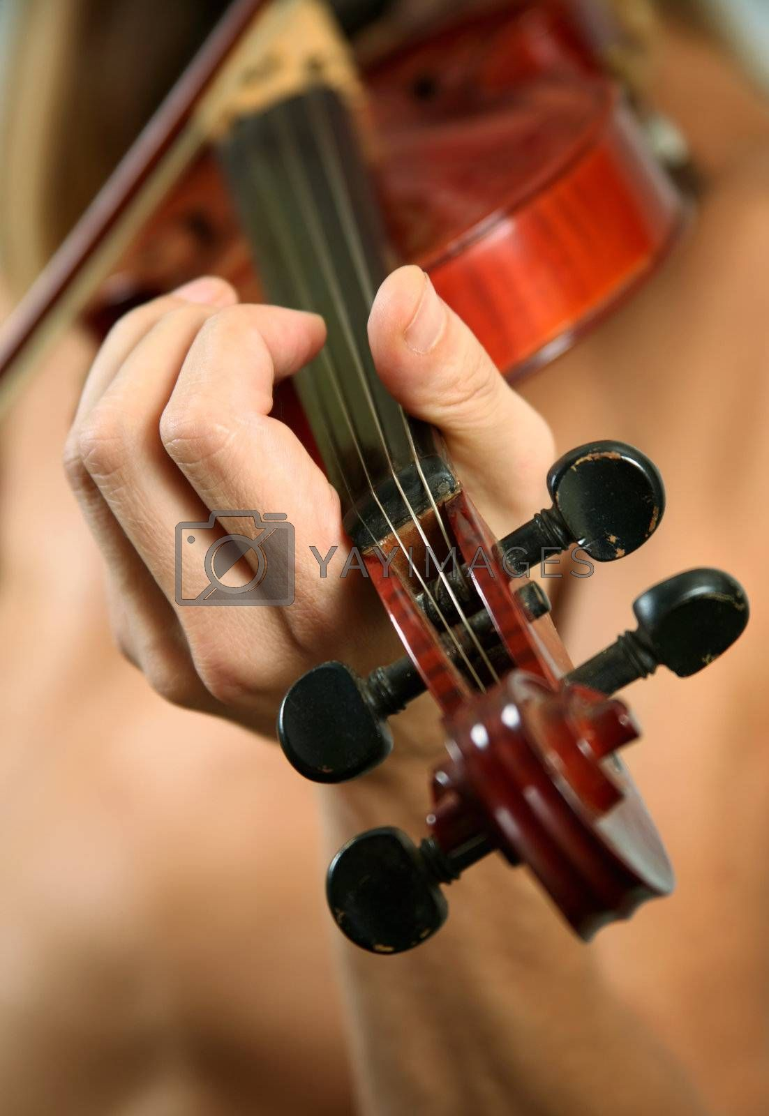 Musician playing violin close-up in studio