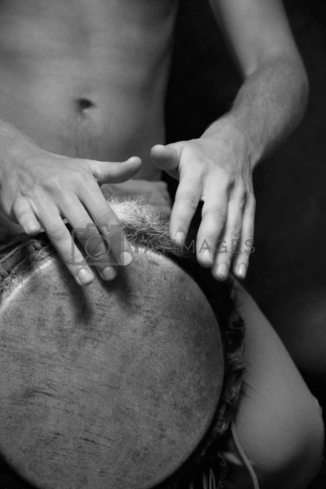 Man playing the djembe (nigerian drum) in studio