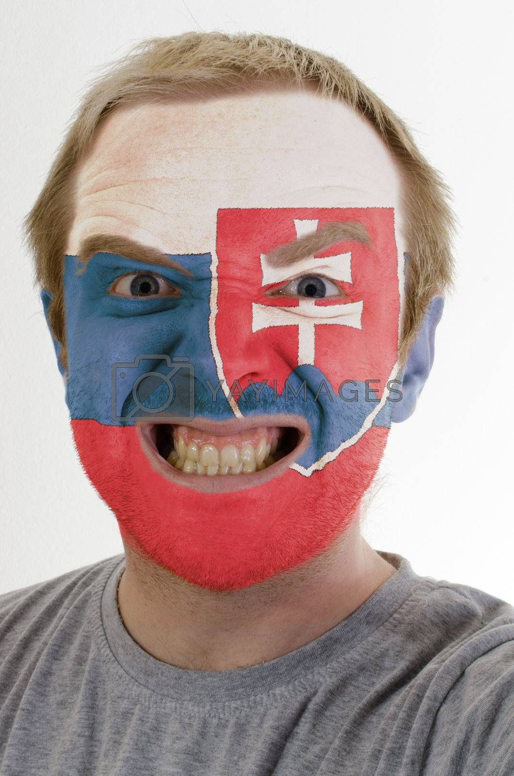 High key portrait of an angry man whose face is painted in colors of slovakia flag