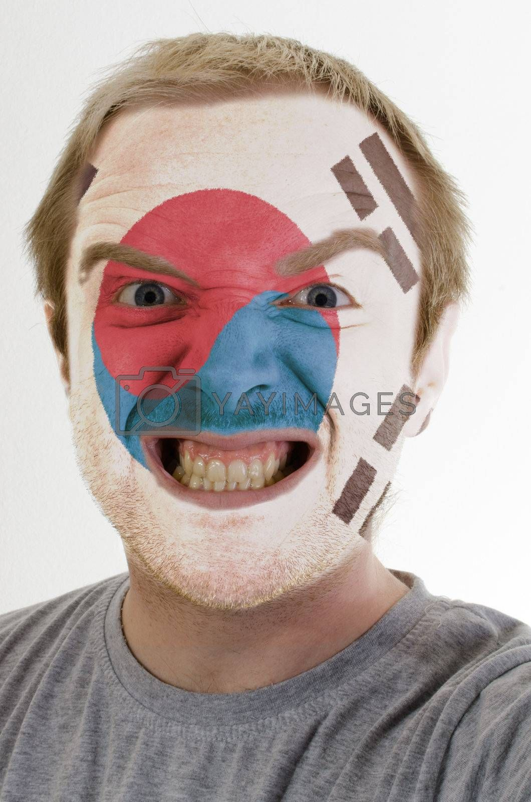 High key portrait of an angry man whose face is painted in colors of south korea flag