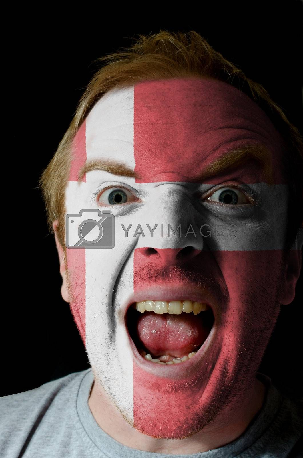 Low key portrait of an angry man whose face is painted in colors of denmark flag