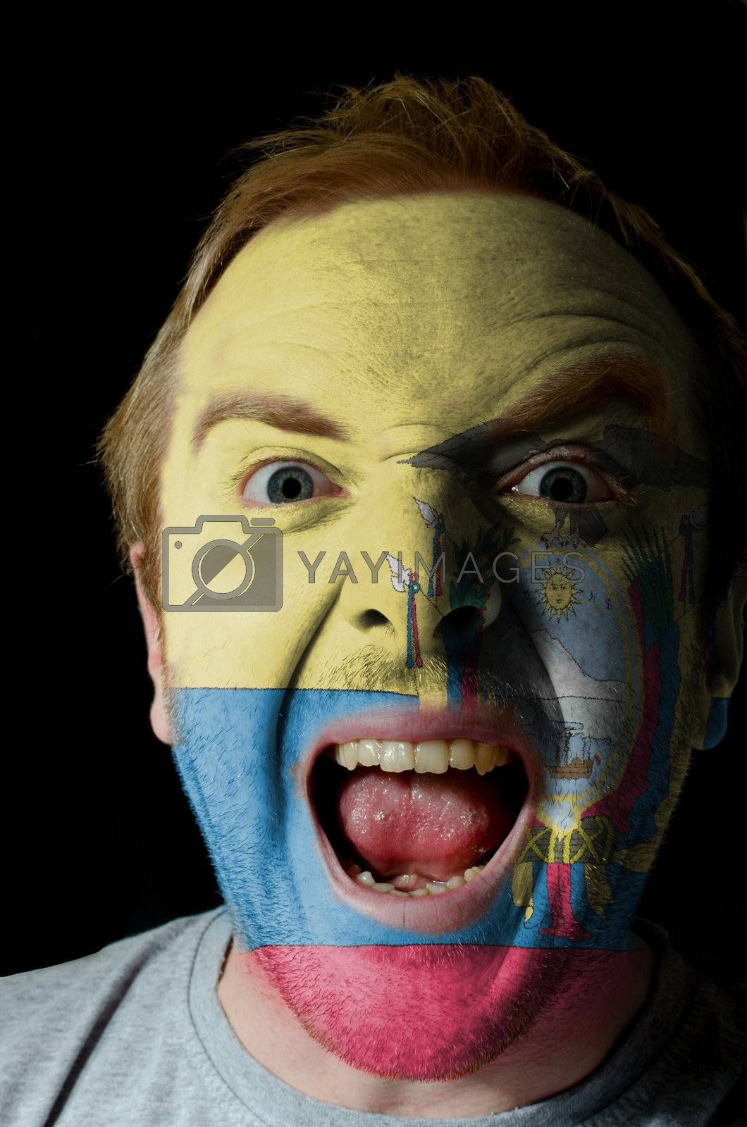 Low key portrait of an angry man whose face is painted in colors of ecuador flag