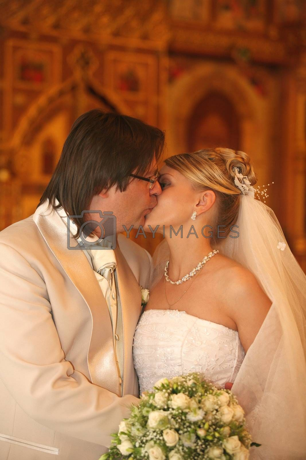 The groom and the bride kiss in church