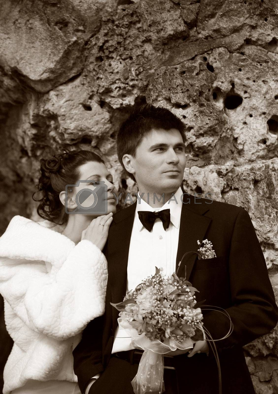 Recently married pair on a background of a stone. b/w+sepia