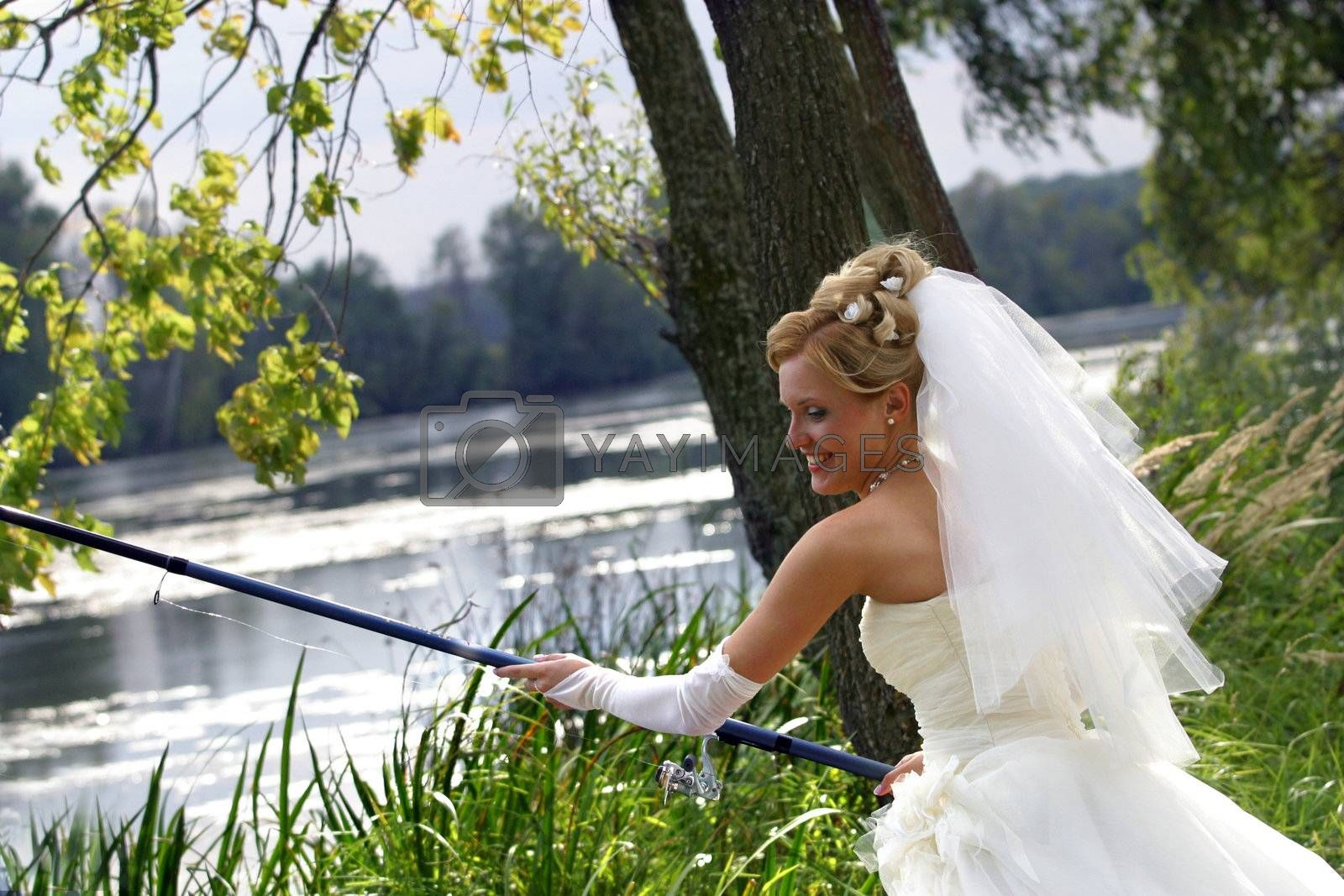 The beautiful bride with fishing tackle