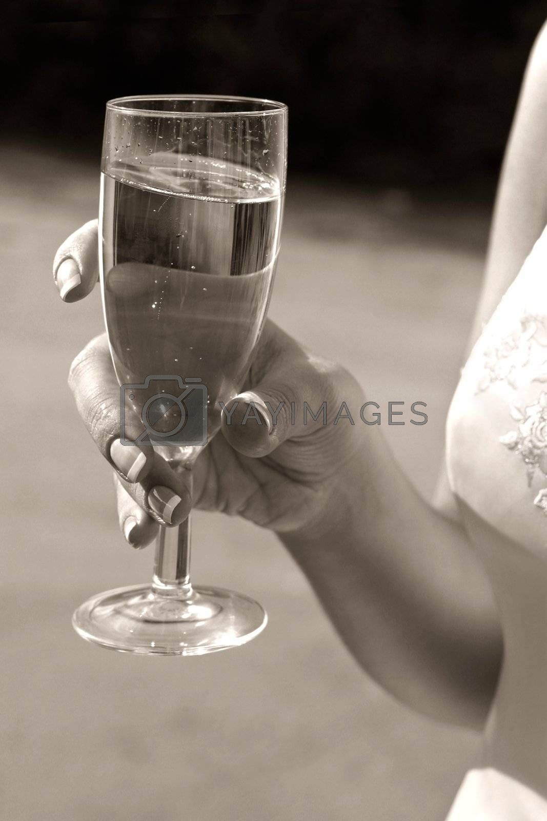 Glass with champagne in hands of the bride. b/w+sepia