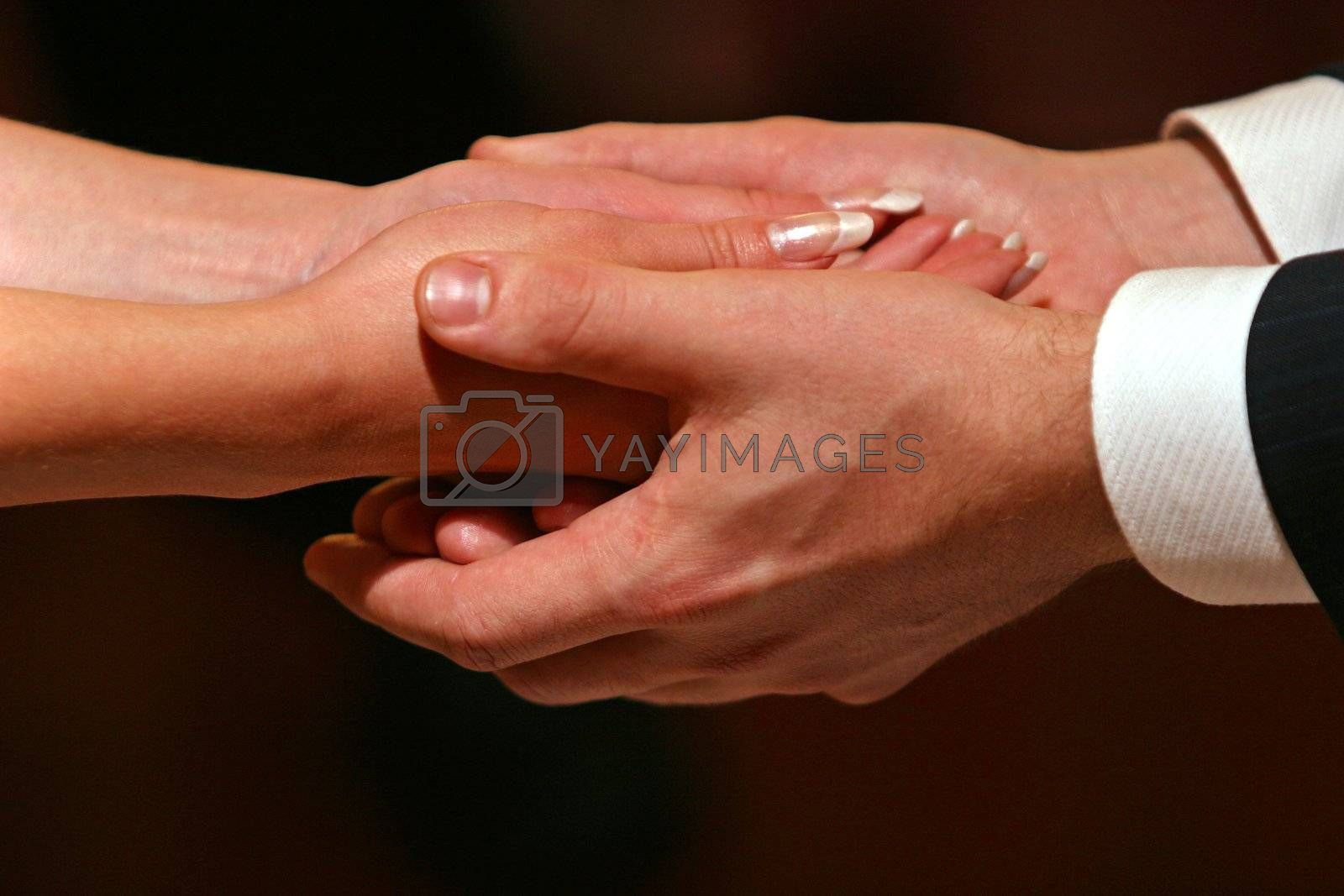 Female hands in man's hands on a dark background