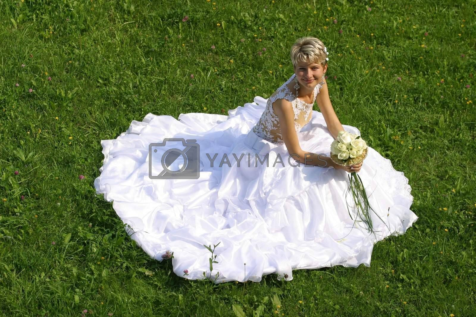 The beautiful bride with a wedding bouquet sits on a grass
