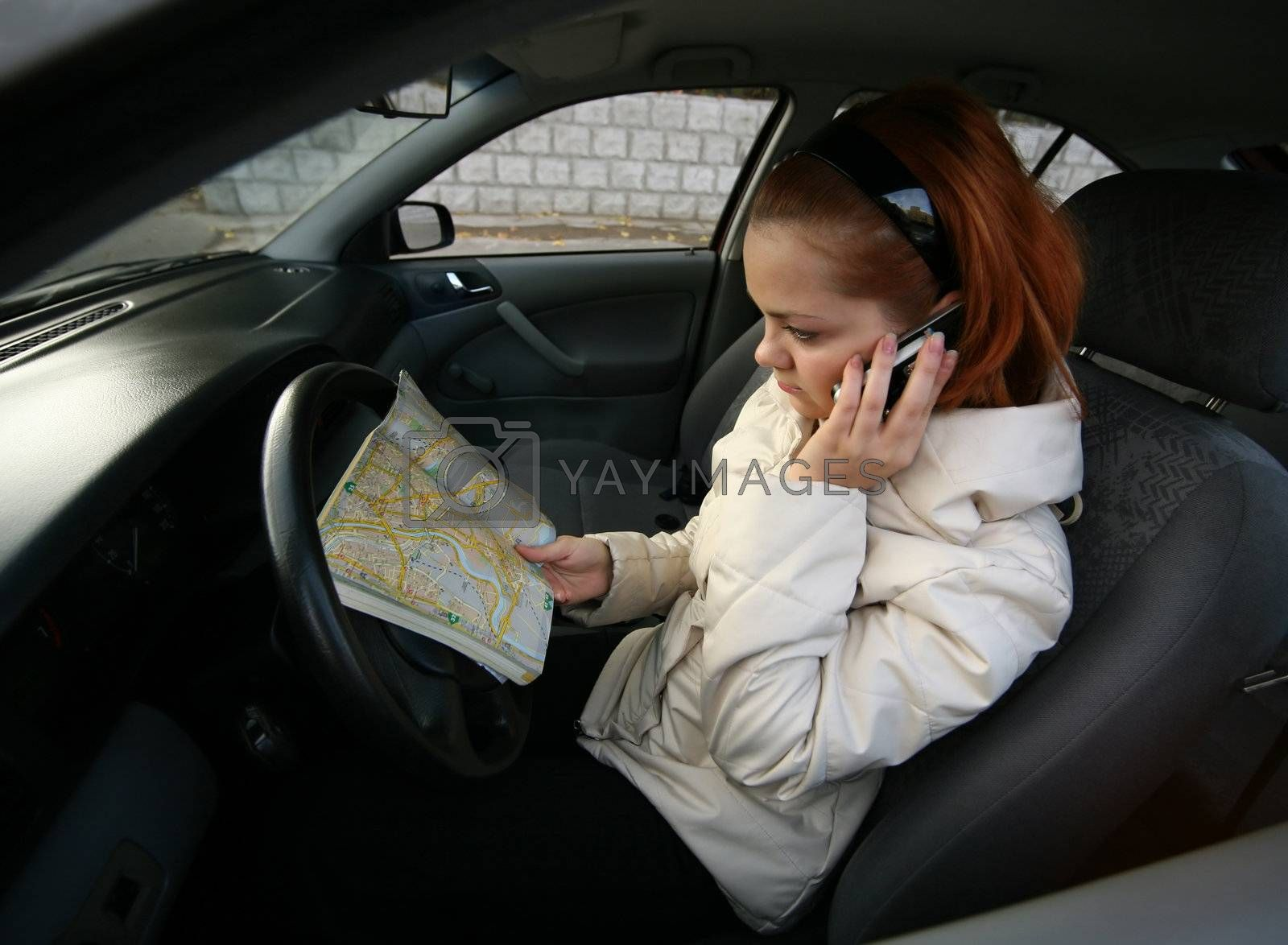 The young girl with a map of streets and the phone in the automobile