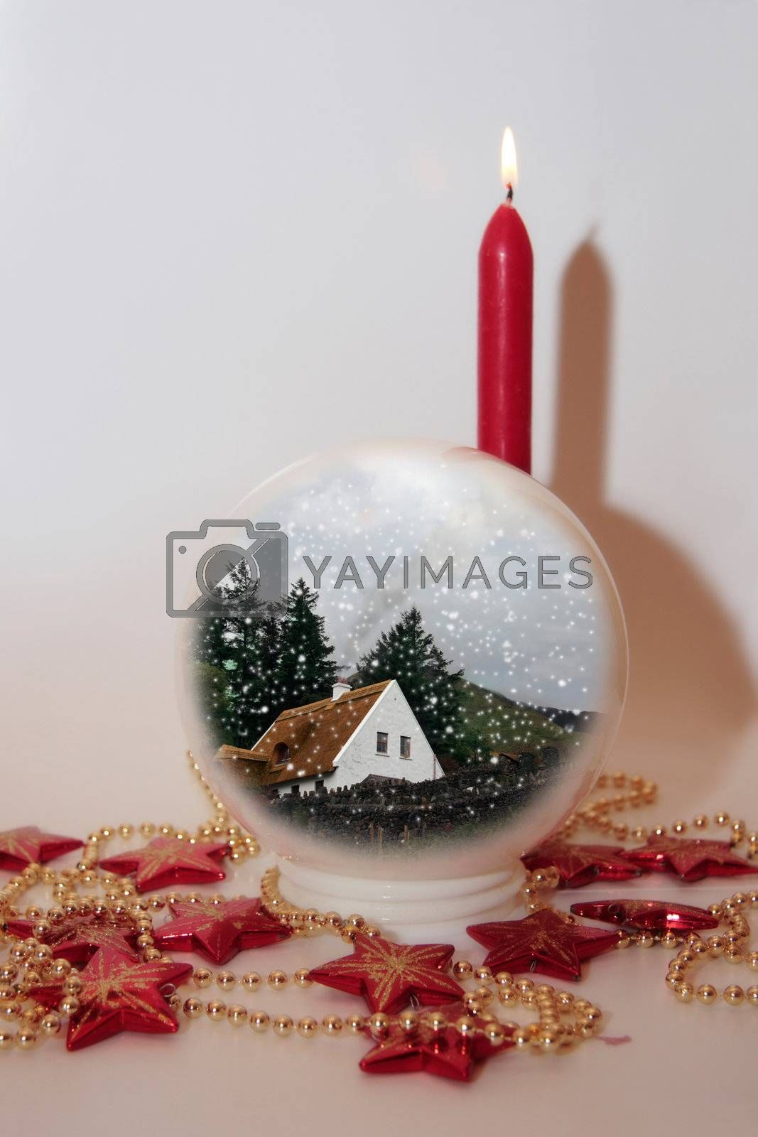 christmas crystal ball against a snowing background with candles
