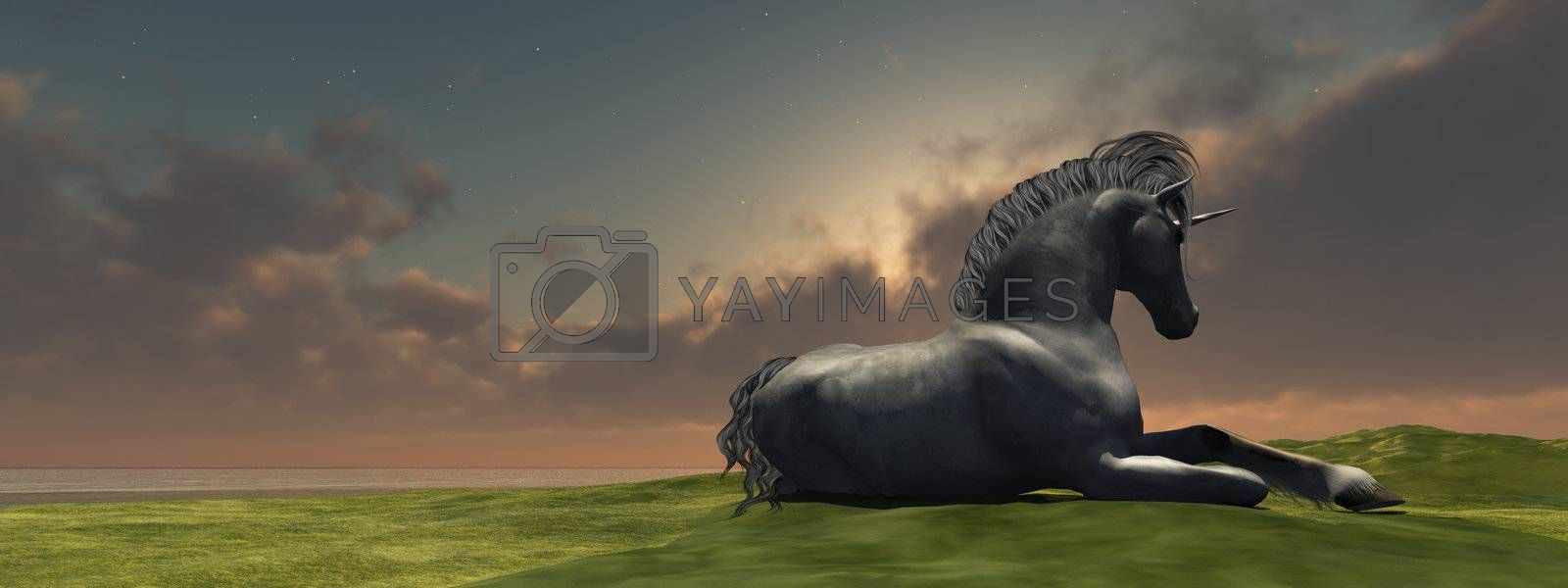 A beautiful unicorn lies down to rest as the sun goes down for the day.