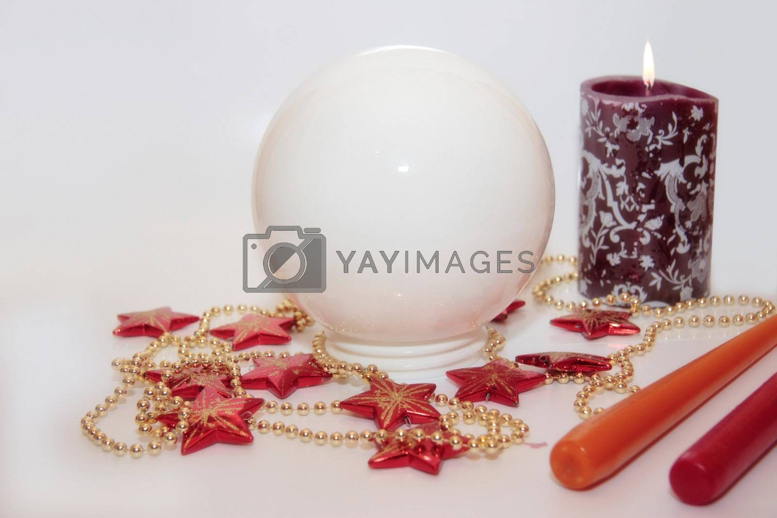 christmas crystal ball against a bright background with candles