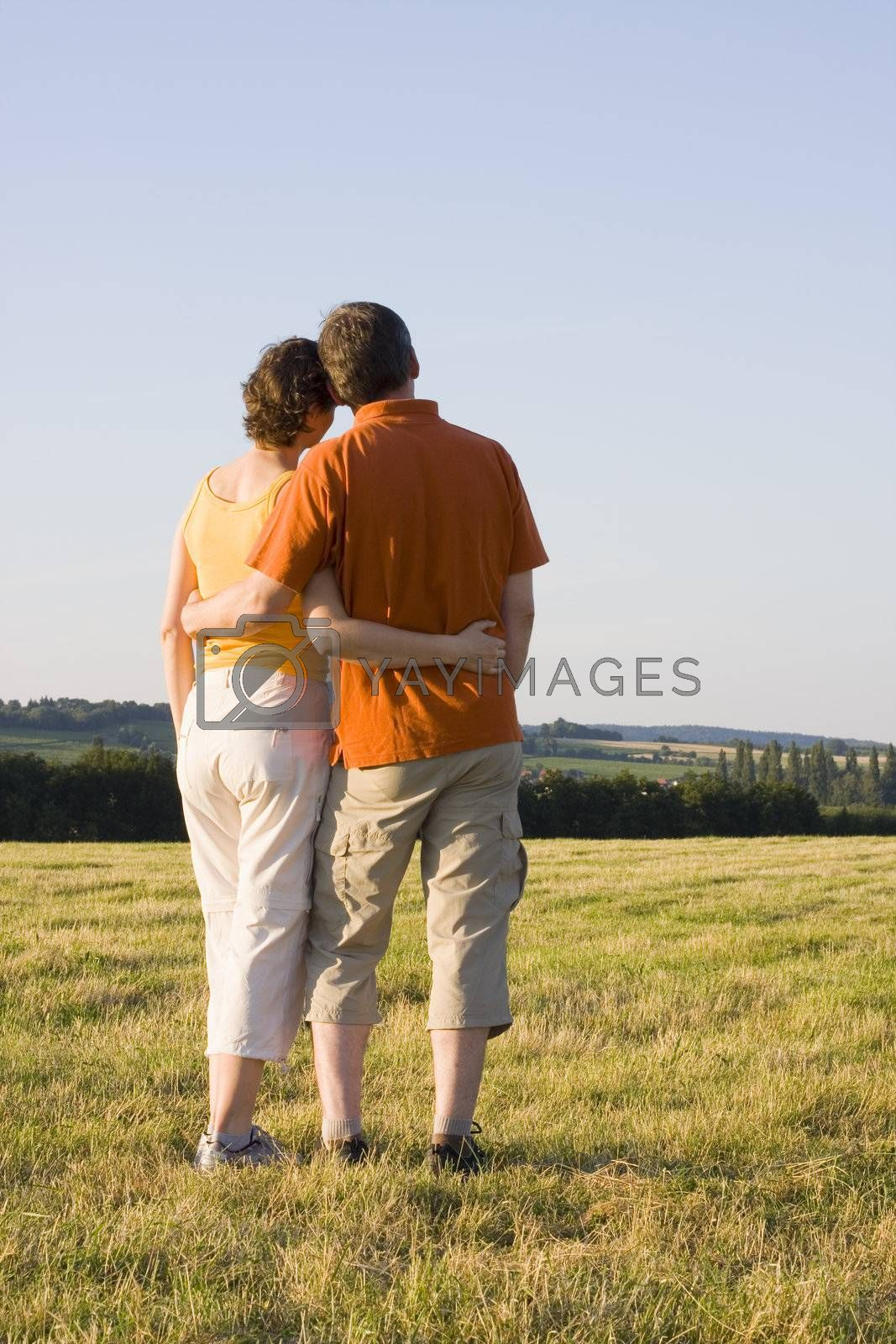 Couple standing arm in arm at sunset in a meadow