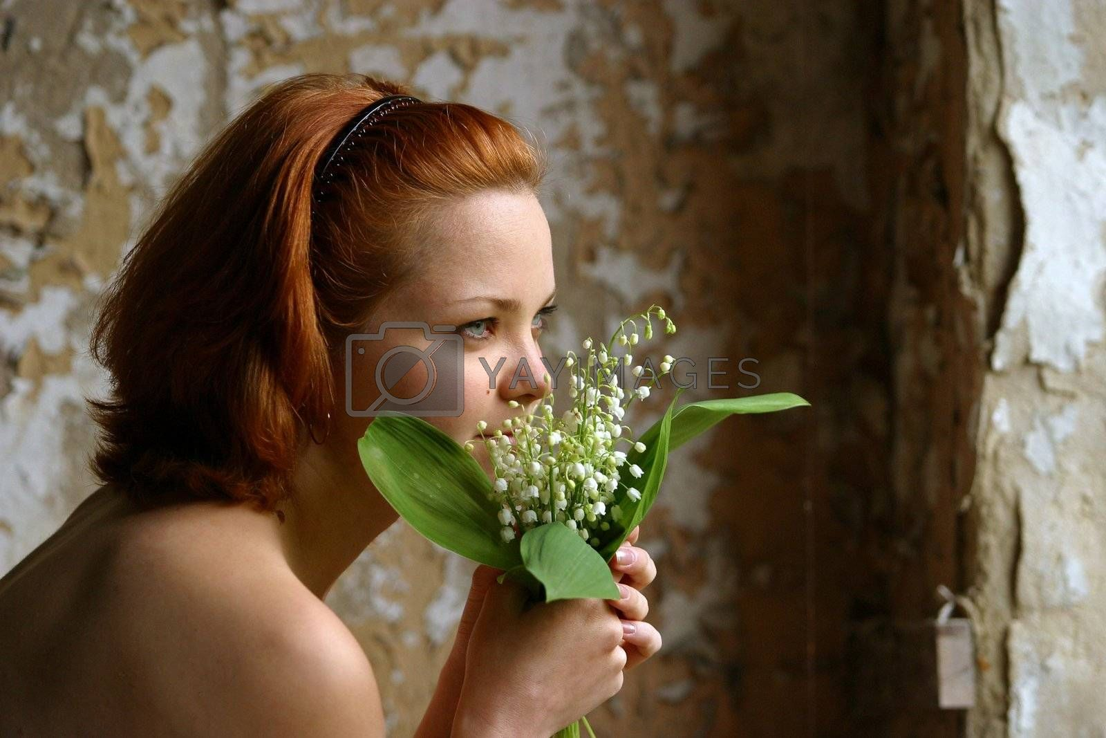 Portrait of the girl with flowers on a background of an old wall