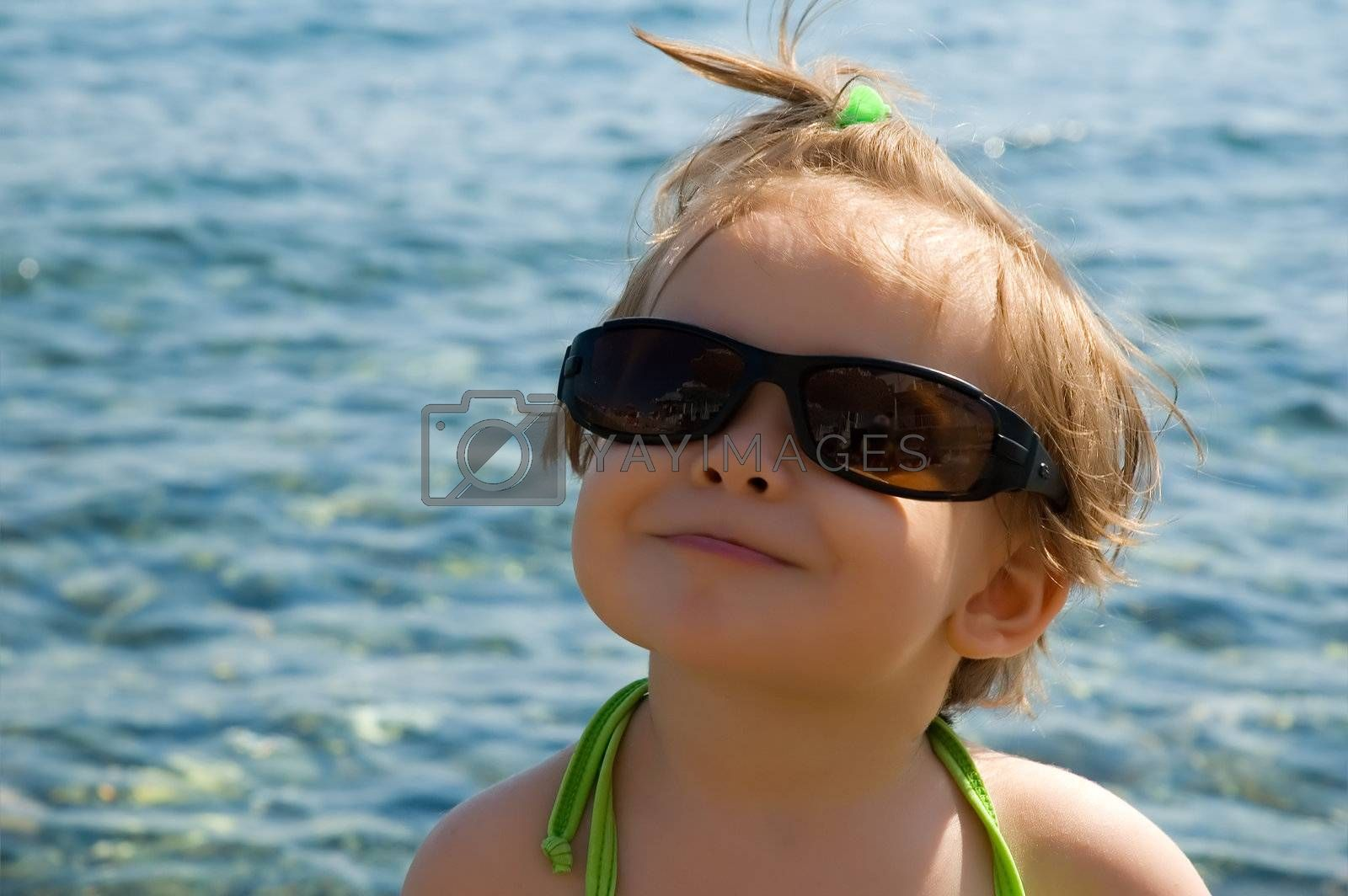 A very cute little girl wearing her mom's sun glasses at the beach