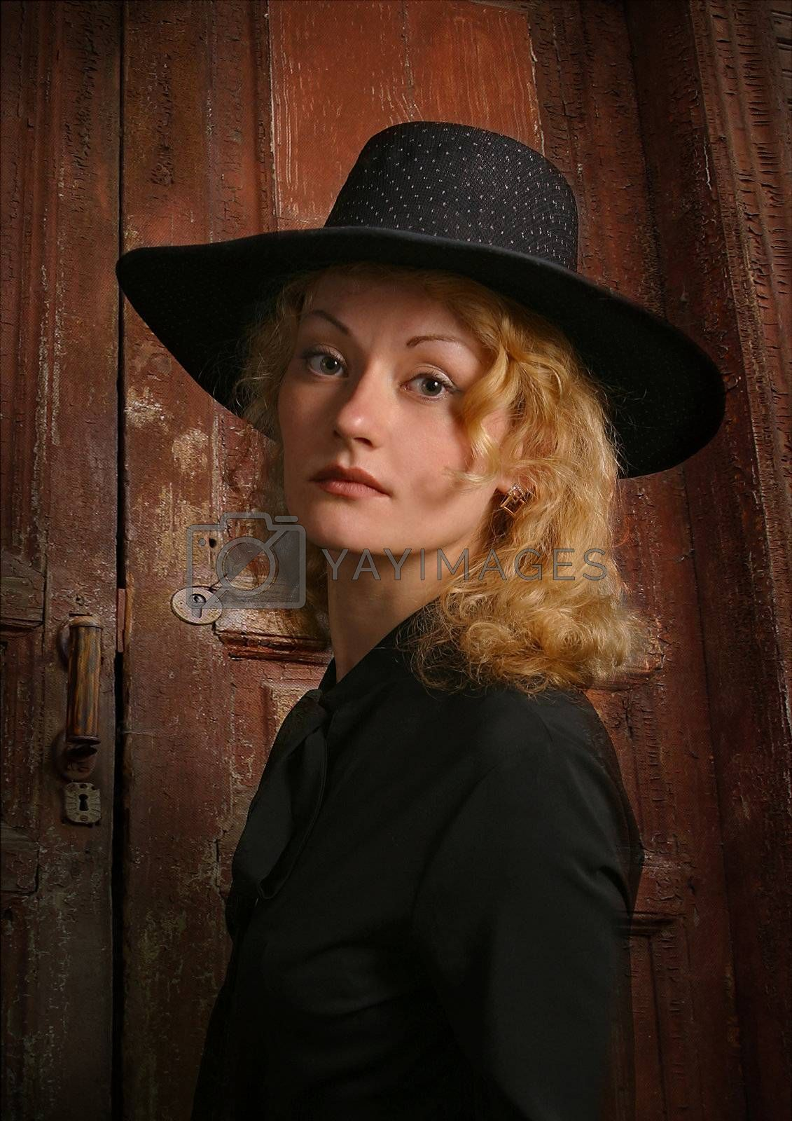 Portrait of attractive lady in a hat on a background of an old door