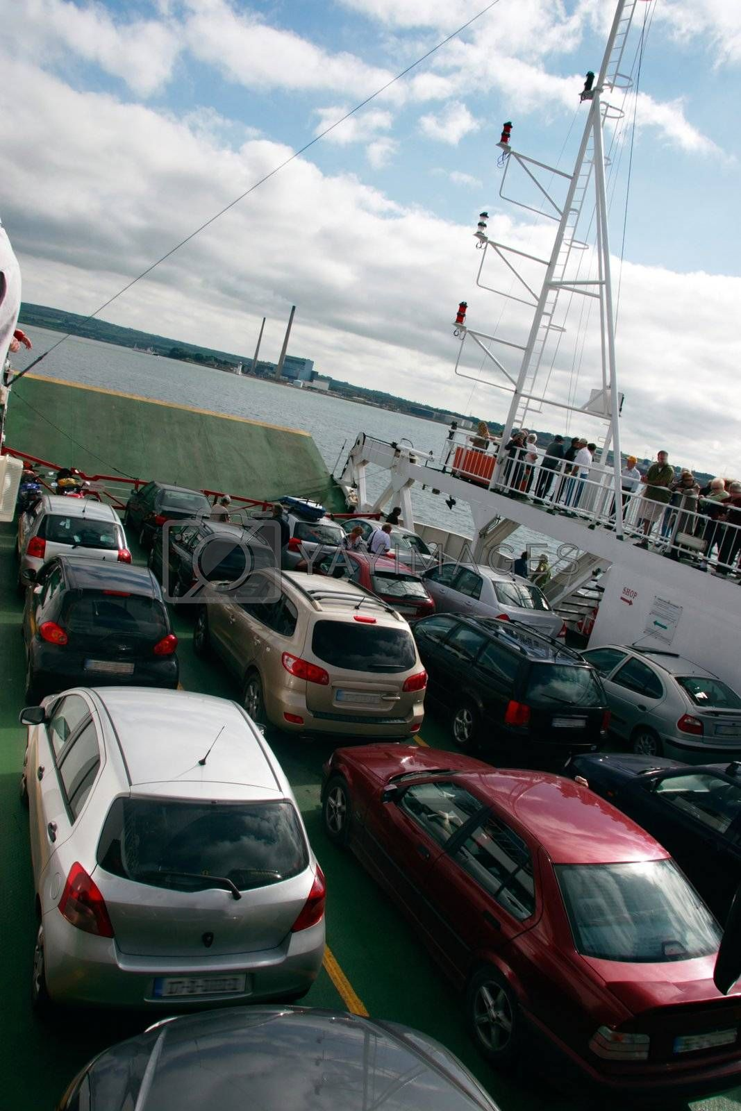 people and cars on the deck of a car ferry