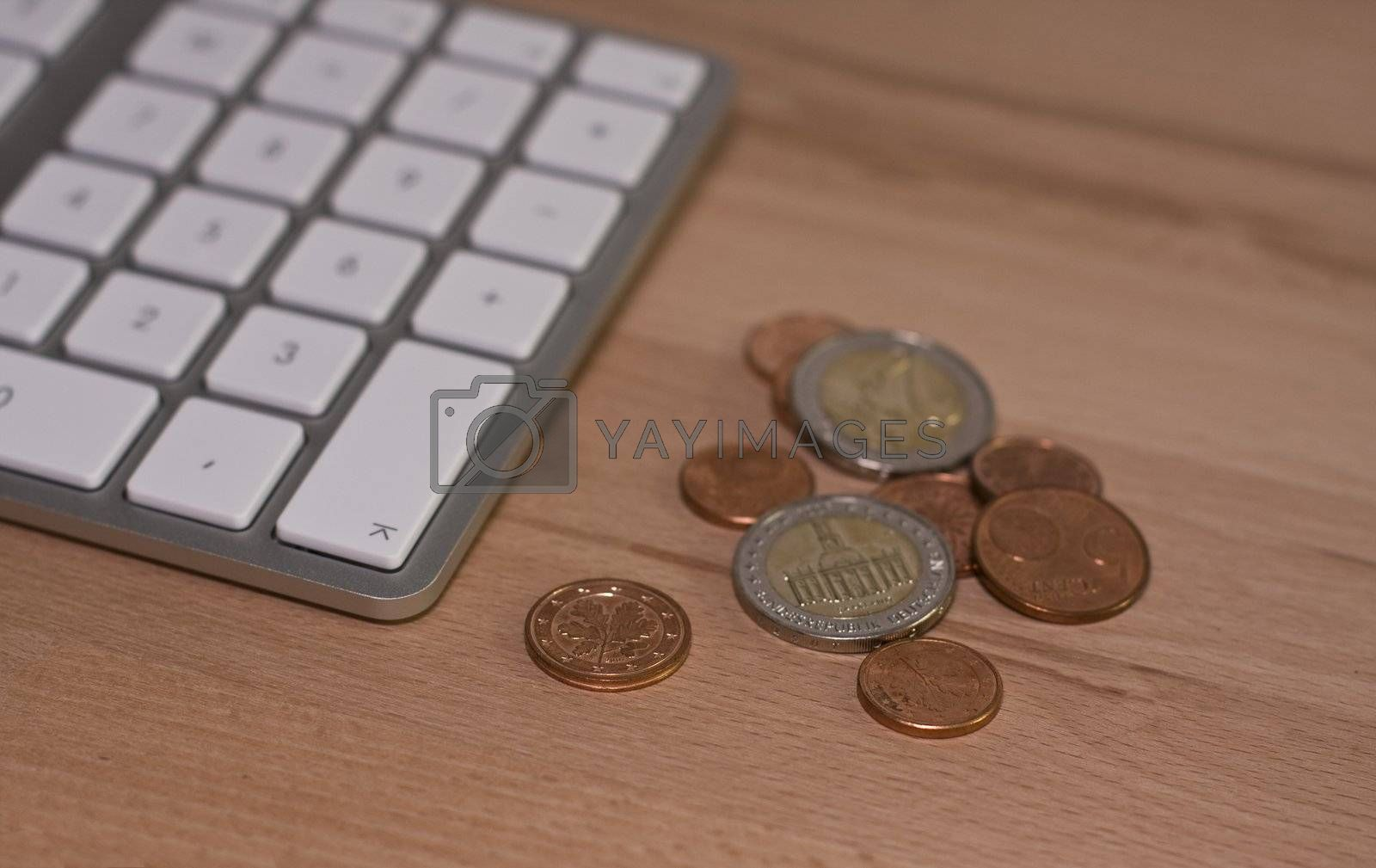 Keyboard and euro coins on wooden desk with nice blur. Place for text