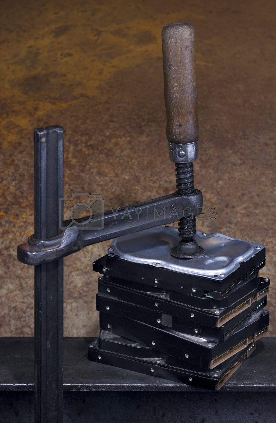 clamp pressing on stack of hard drives. The top drive is deformed