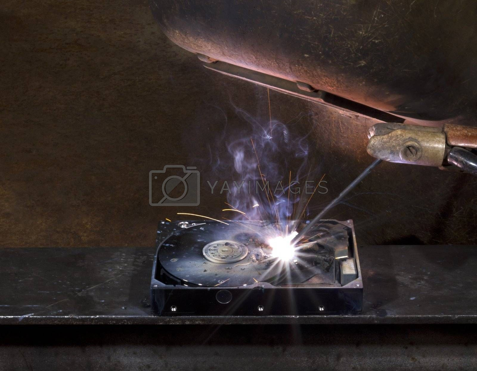 repairing a defect hard disk with welding apparatus. Protective shield and smoke on rusty background