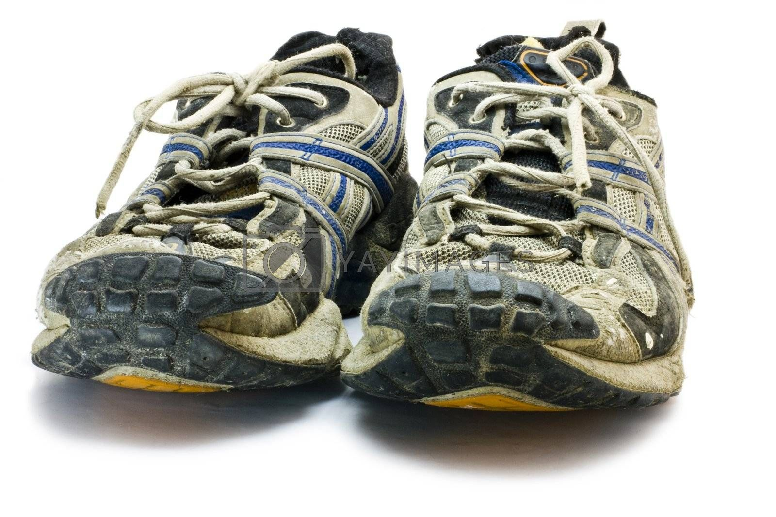 old dirty sports shoes in front view. Low angle.