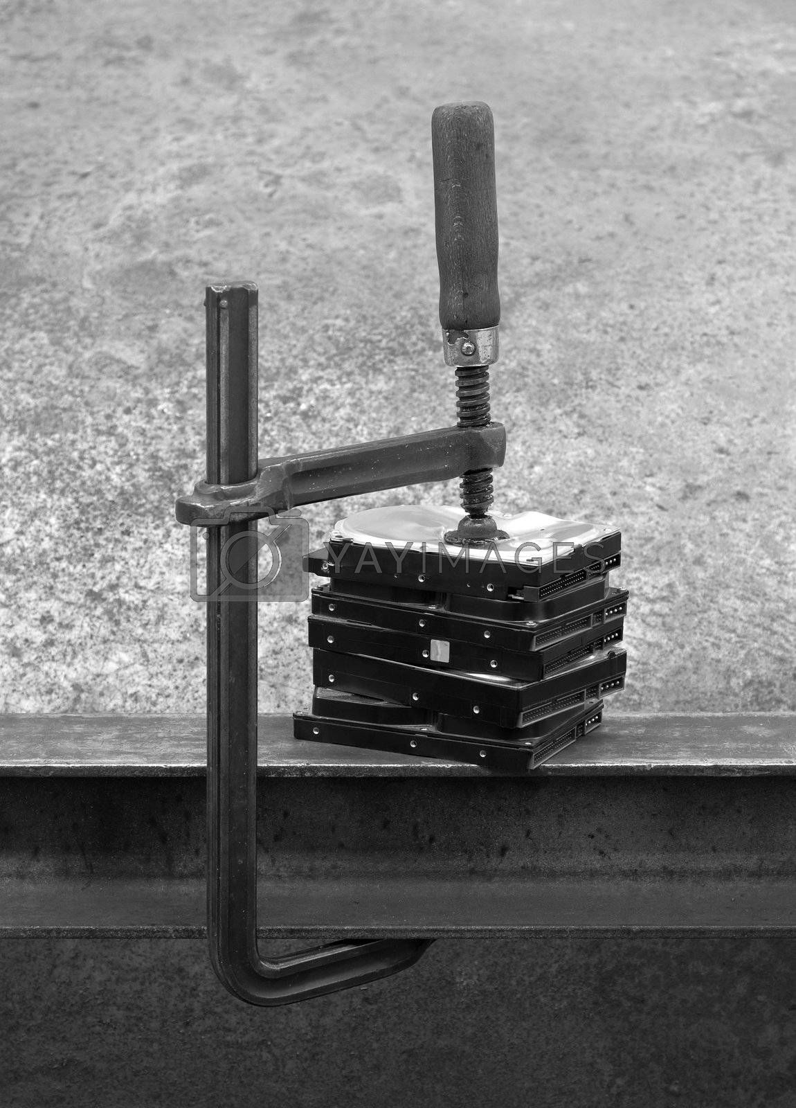 compressed stack of hard disks by clamp. black and white shot