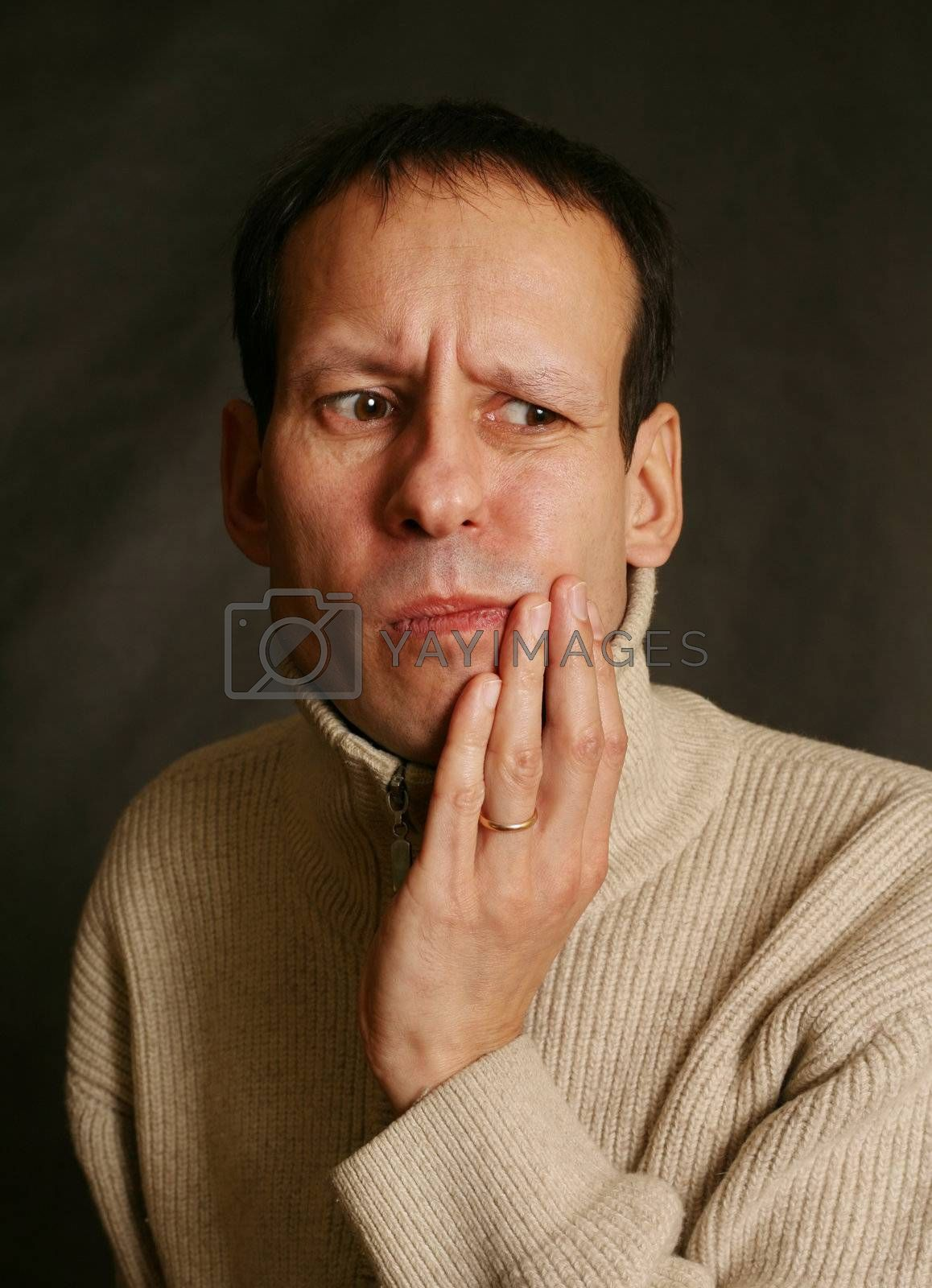 Adult man with toothache on dark background