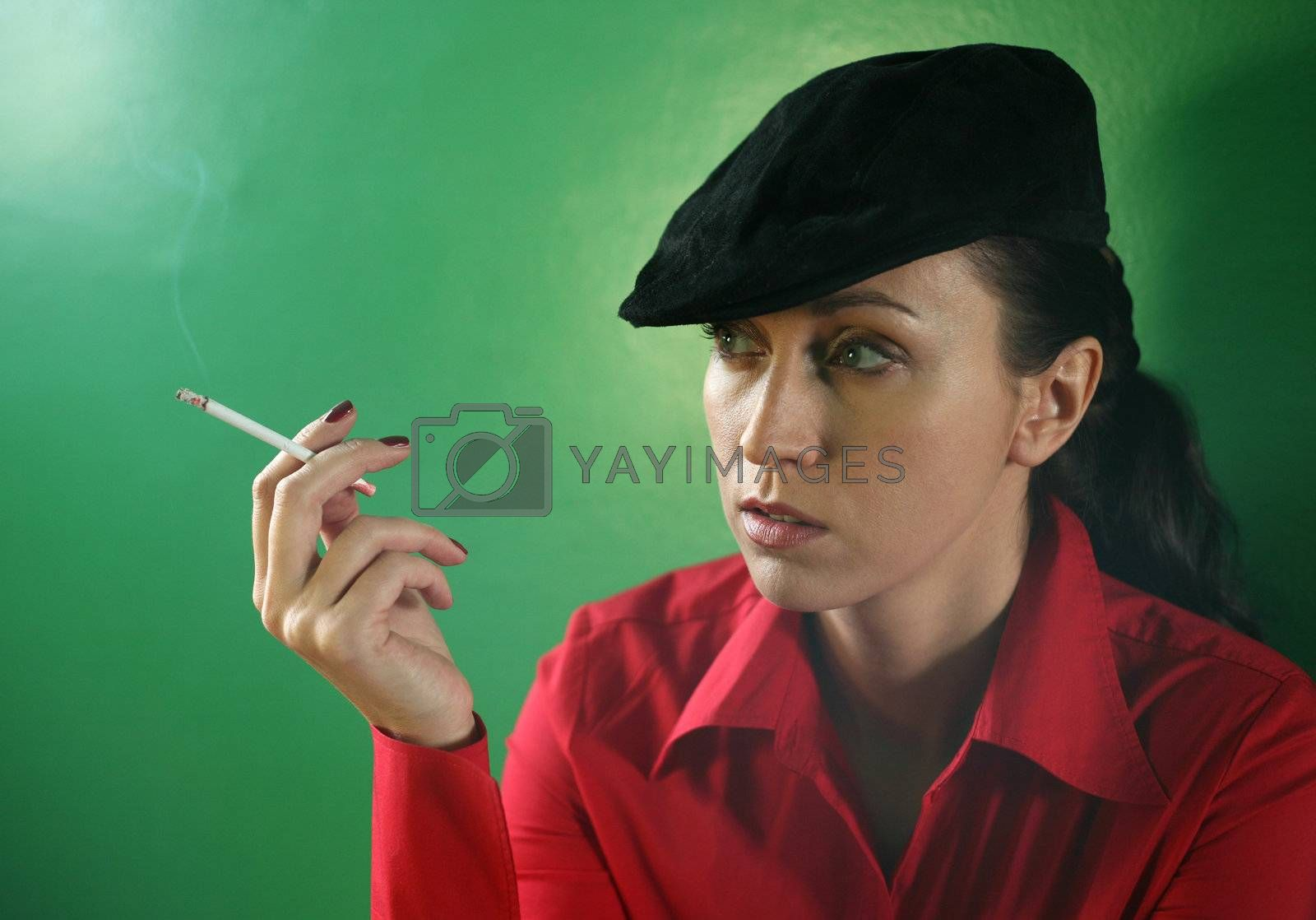 Woman with a cigarette on green background