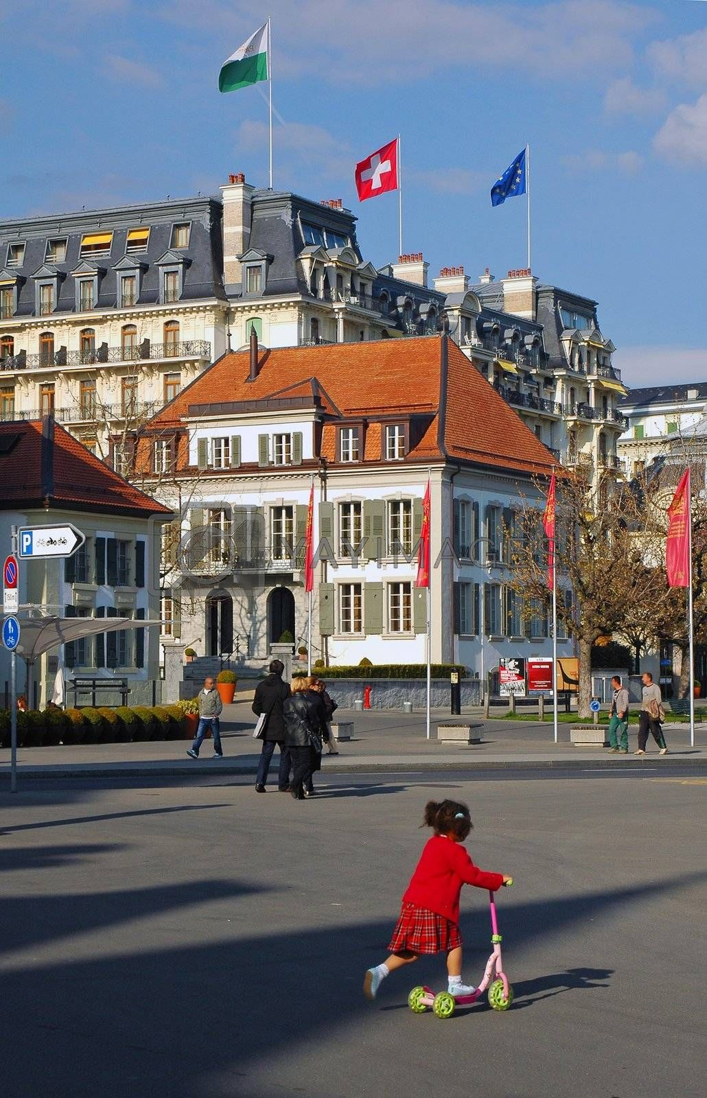 Street scene in Lausanne Switzerland showing various pedestrians and little girl with red sweater on bike.