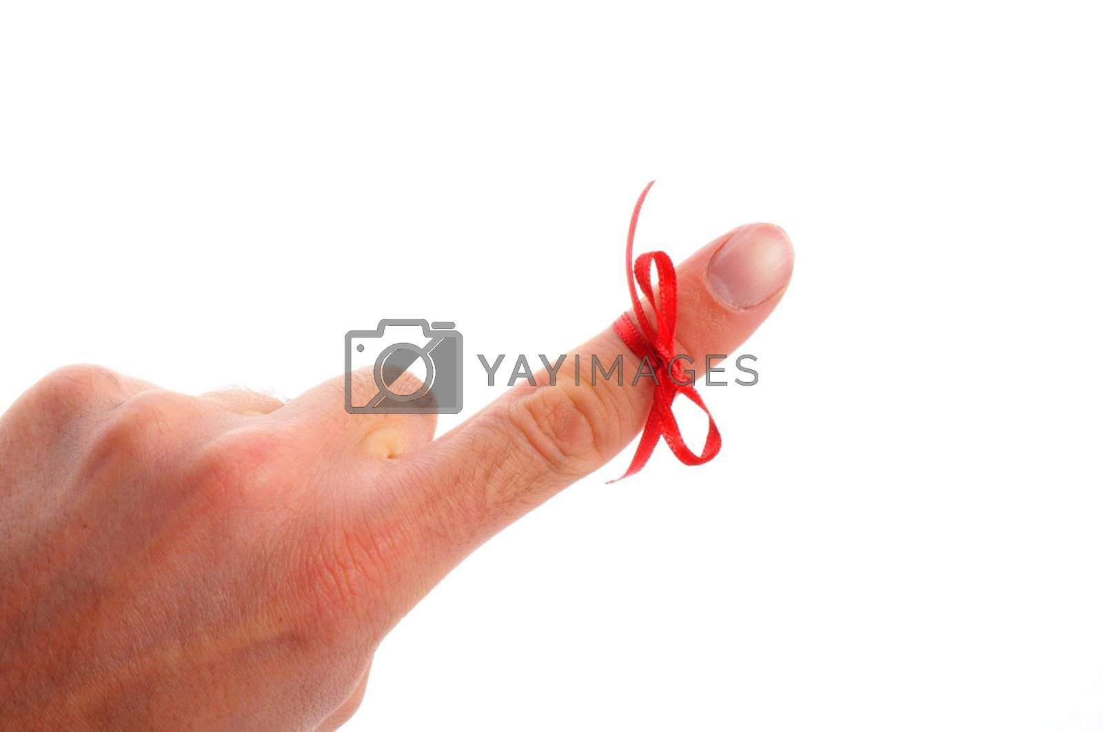 red bow on male finger showing reminder or dont forget concept in white