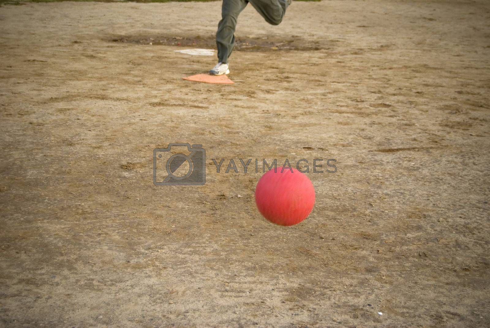 A red kickball rolls toward home plate after it is pitch - the person pictured here on plate is approaching the kick.
