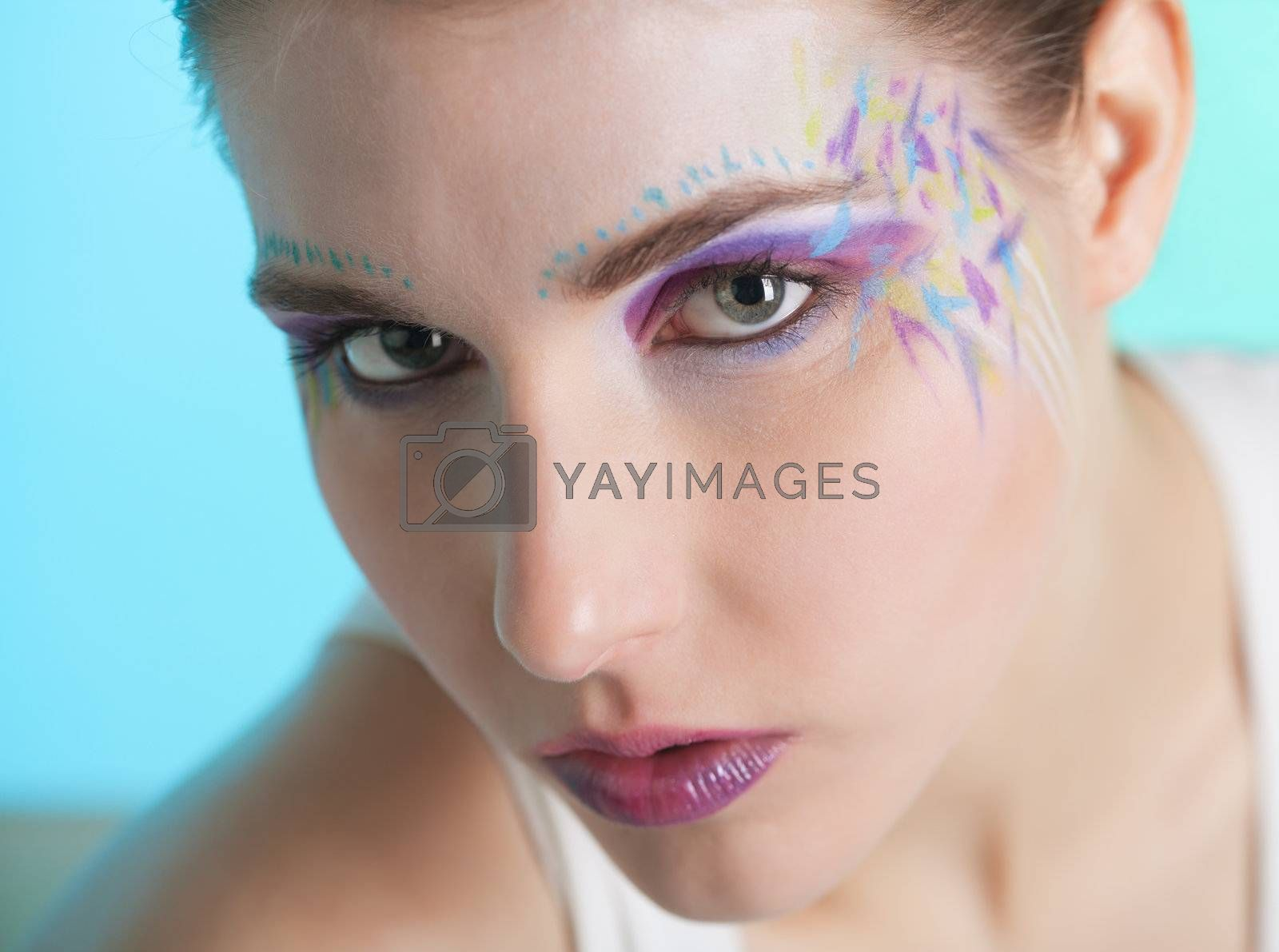Closeup portrait of a pretty young woman with face art