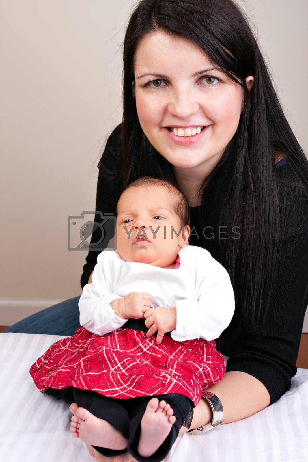 A newborn baby being held in the arms of her mother.