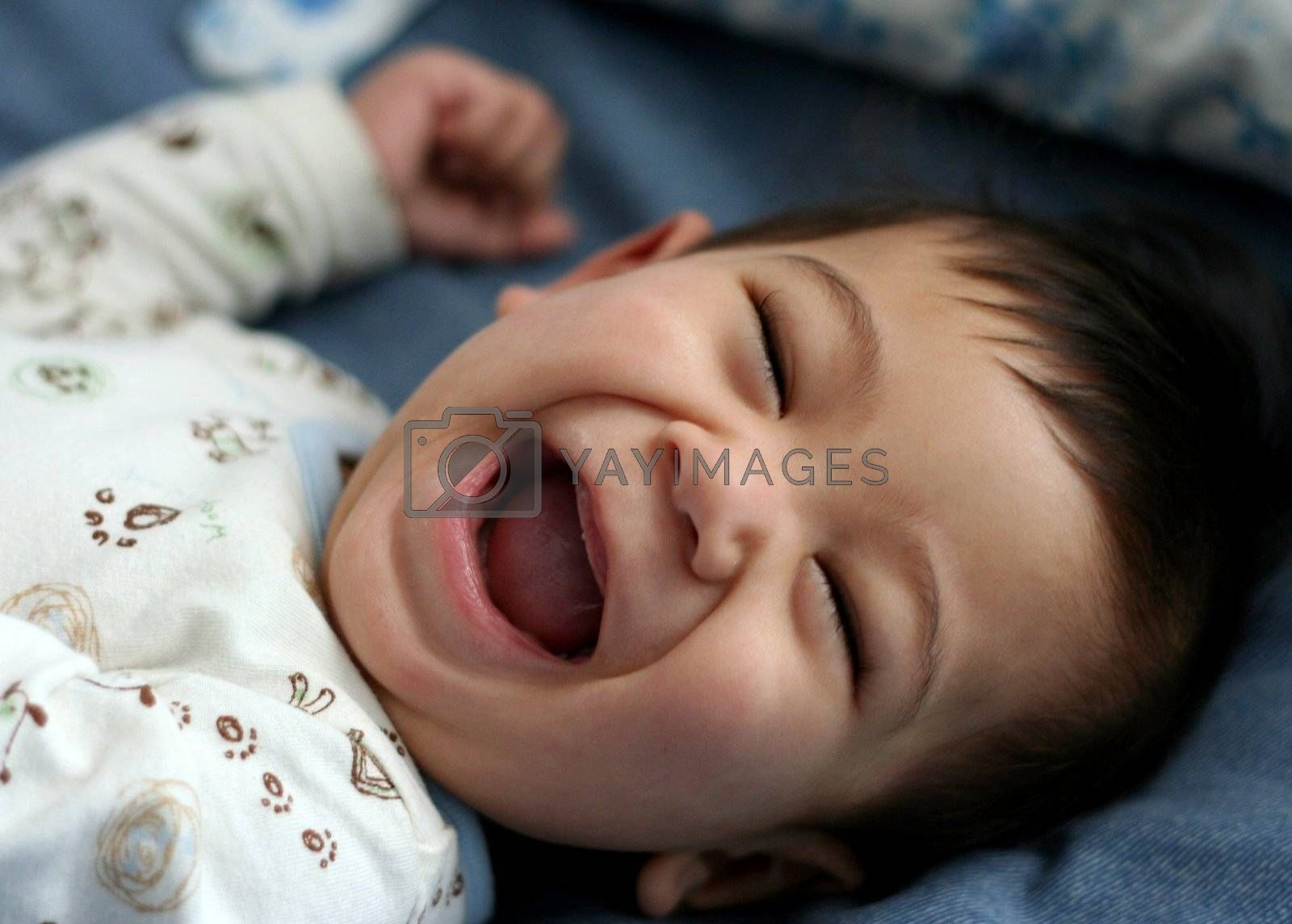 Happy six month old baby on bed